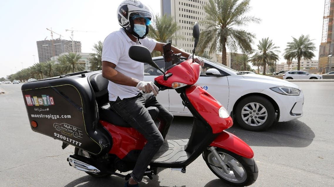 A delivery man rides his motorbike to deliver food orders for customers, as restaurants are closed, following the outbreak of coronavirus, in Riyadh, Saudi Arabia, March 17, 2020. (Reuters)