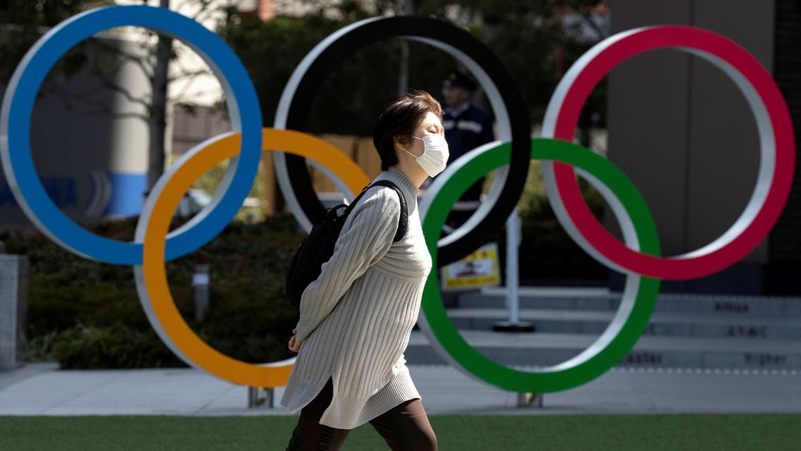 A woman wearing a protective face mask, following an outbreak of the coronavirus disease (COVID-19), walks past the Olympic rings in front of the Japan Olympics Museum in Tokyo, Japan March 13, 2020.  (Reuters)