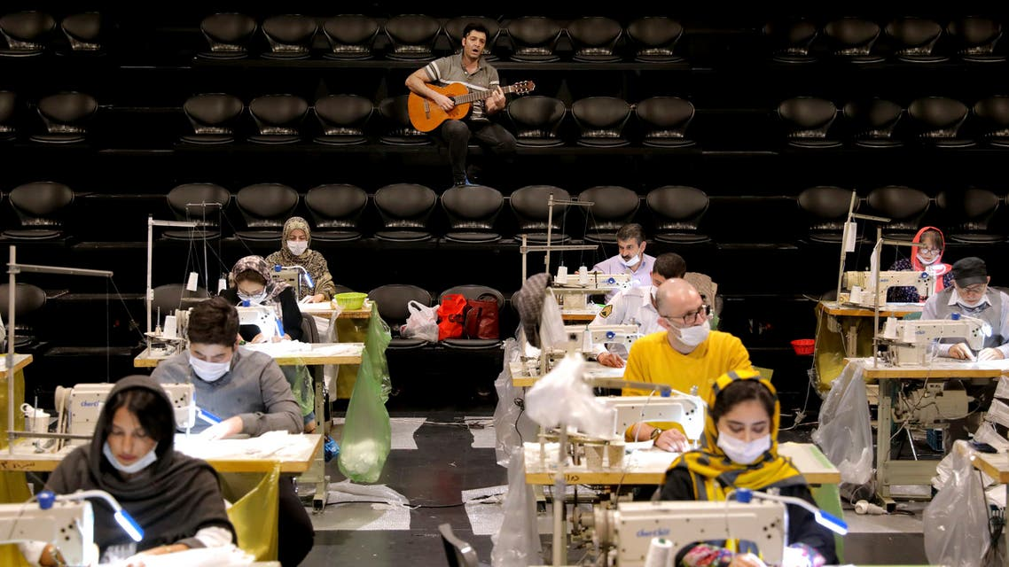 Volunteers wearing face masks to curb the spread of the new coronavirus, sew face masks, as a guitarist plays for volunteers, at the Hafez theatre hall in downtown Tehran, Iran, Wednesday, April 15, 2020. (AP