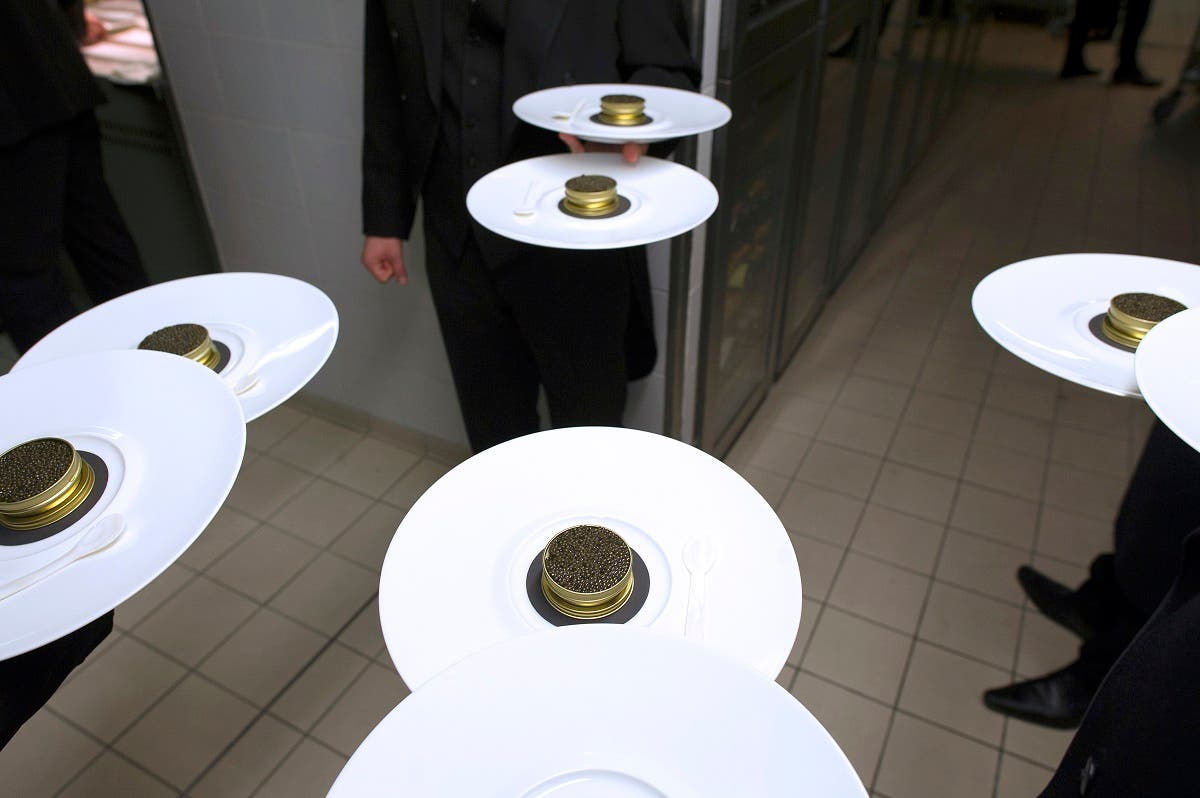 Waiters of the five-star luxury hotel Le Bristol in Paris hold plates with caviar in the hotel's kitchen. (AFP)
