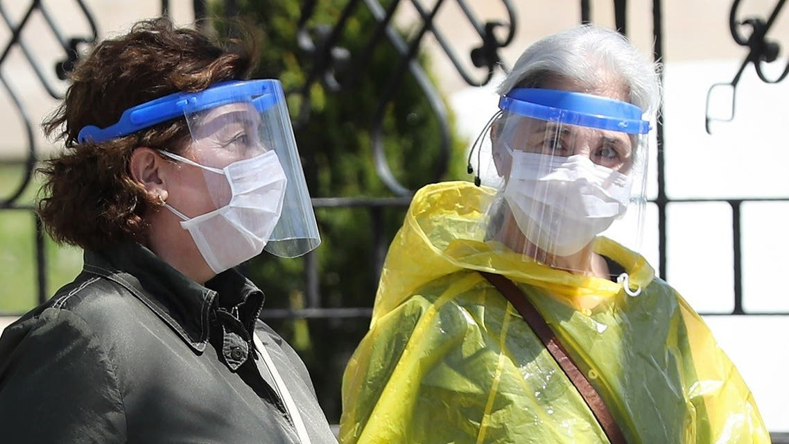 Two women wearing protective facemasks and face-shields, speak together as they walk in the streets of Ankara. (AFP)