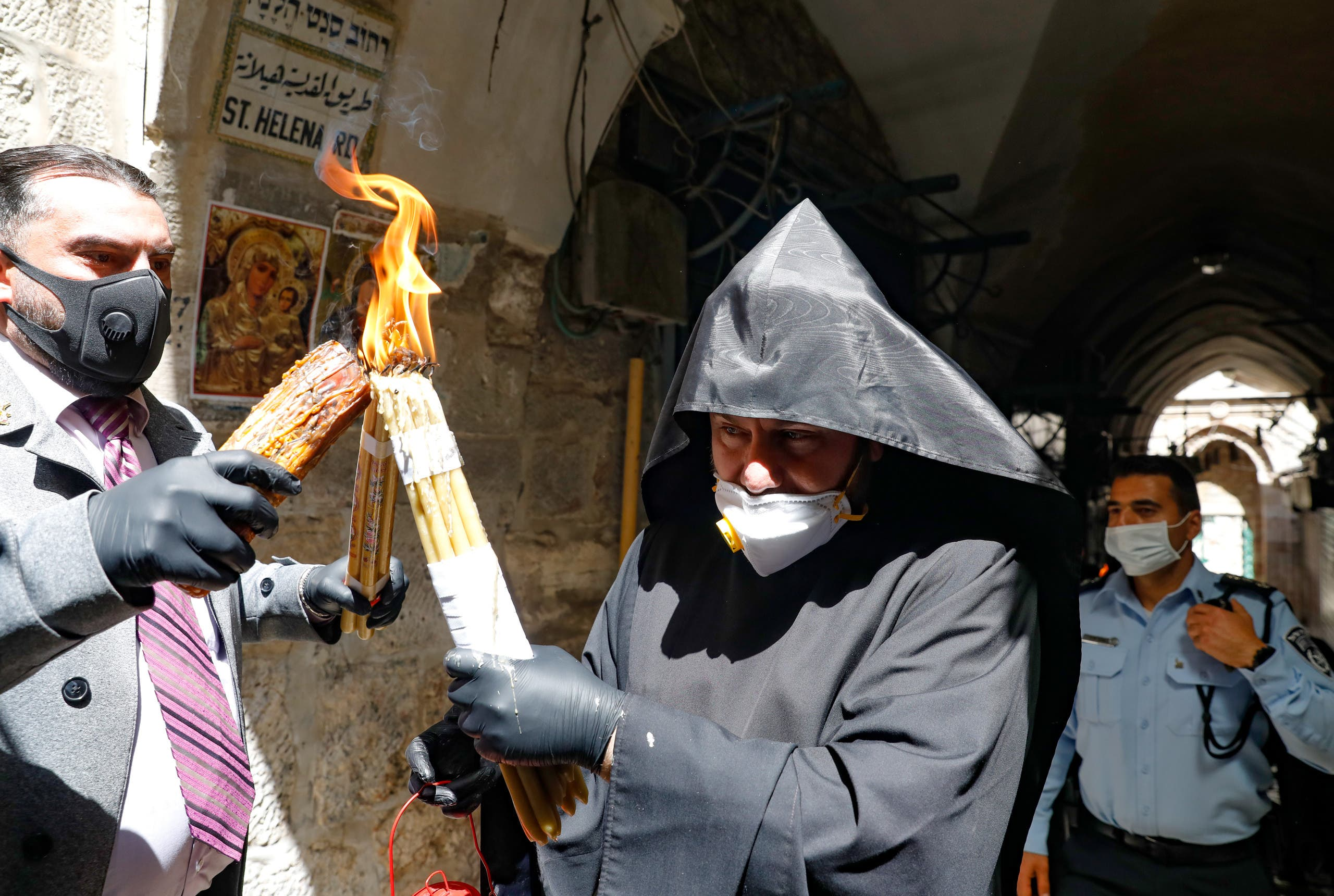 An Armenian priest wearing a protective mask and gloves passes on the Holy Fire lit in the church of the Holy Sepulchre, as very few Orthodox Christians gather in Jerusalem's Old City to celebrate Easter due to the lockdown imposed by authorities in a bid to limit the spread of the novel coronavirus, on April 18, 2020. (AFP)