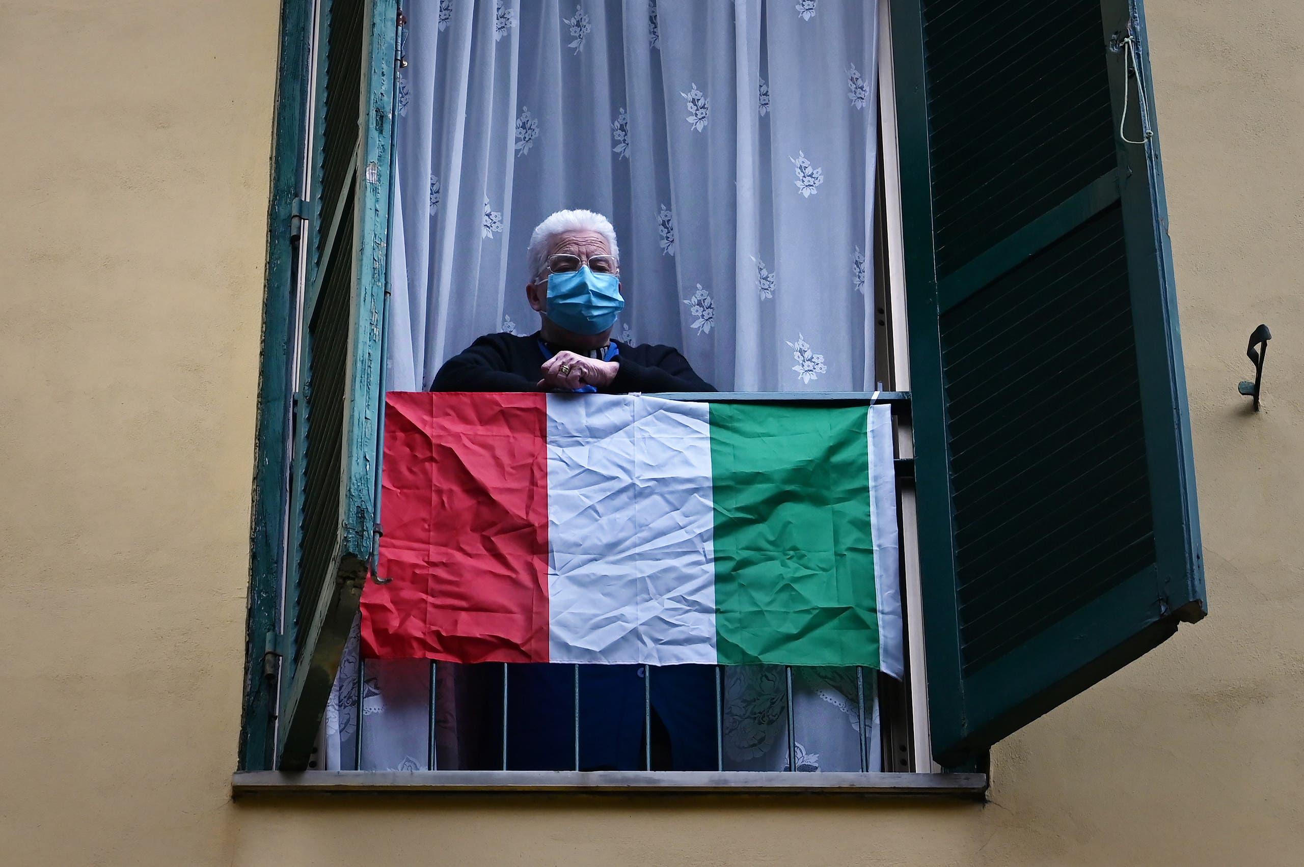 مسن إيطالي يطل من النفاذة في روما مرتدياً كمامة