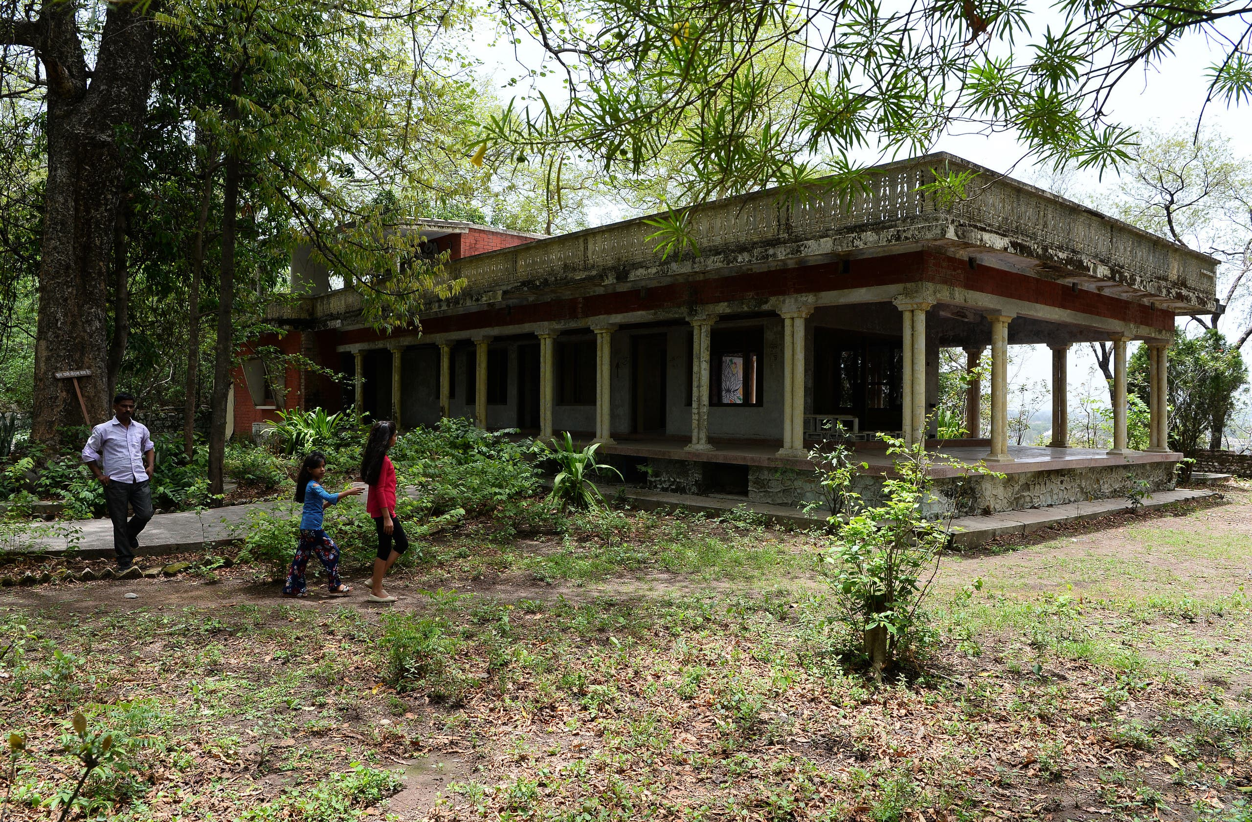 Tourists walking past the now-derelict house of the Maharishi Mahesh Yogi at the ashram visited by the Beatles 50 years ago, in Rishikesh in northern India on June 18, 2018. (AFP)