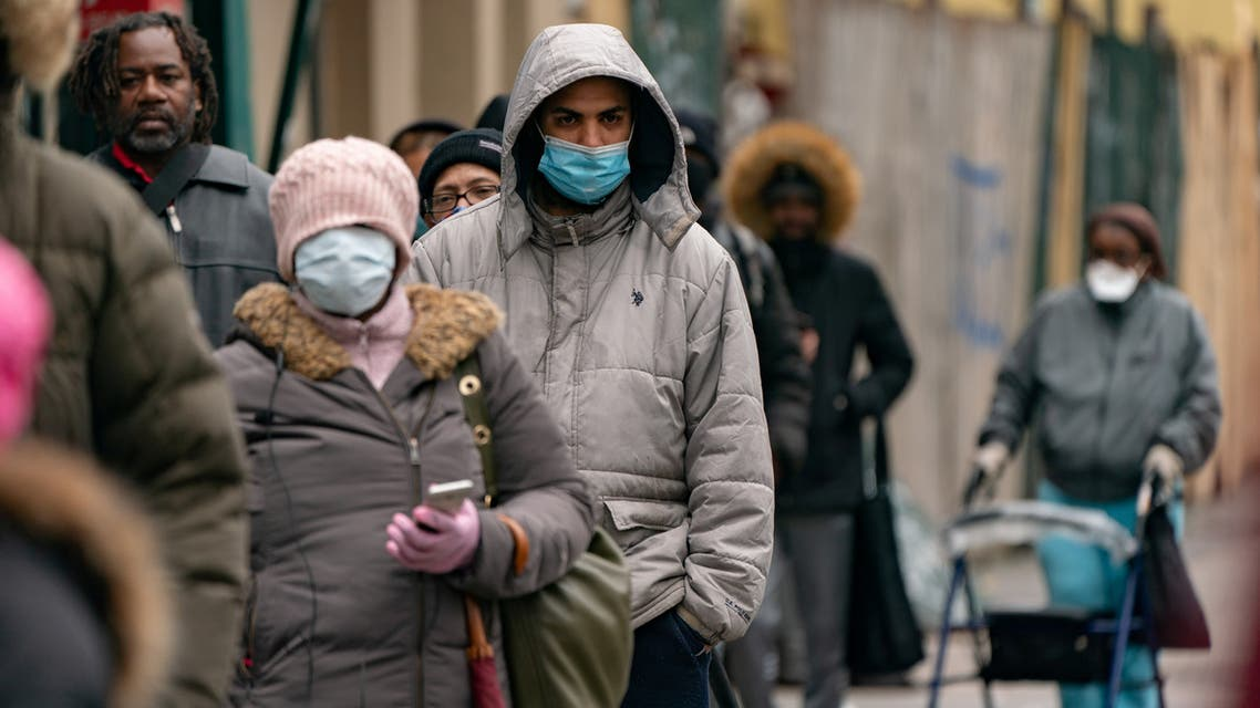 People wearing protective masks wait in line for free masks and pre-packaged meals during the outbreak of the coronavirus disease (COVID-19) in New York City, U.S., April 18, 2020. REUTERS/Jeenah Moon