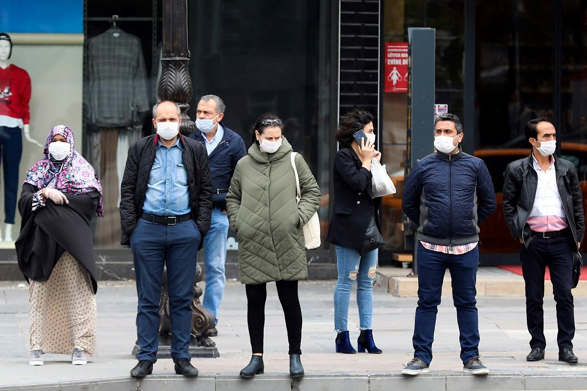 People wearing a facemask for protective measures wait to cross the street as the spread of the COVID-19, the novel coronavirus continues in Ankara. (AFP)