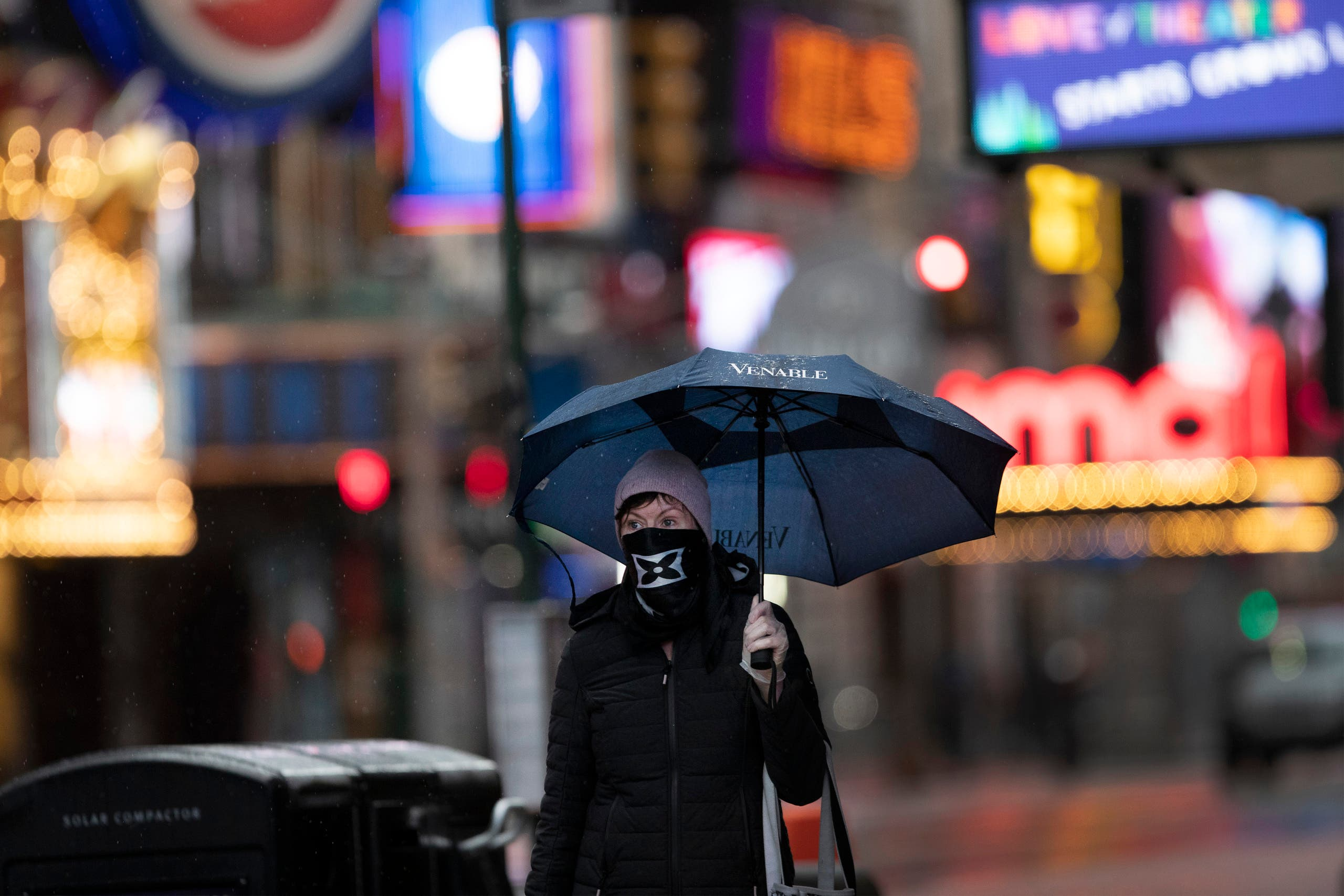 A woman wearing a mask and gloves walks through a rain storm in New York's Times Square on April 9, 2020, during the coronavirus epidemic. (AP)