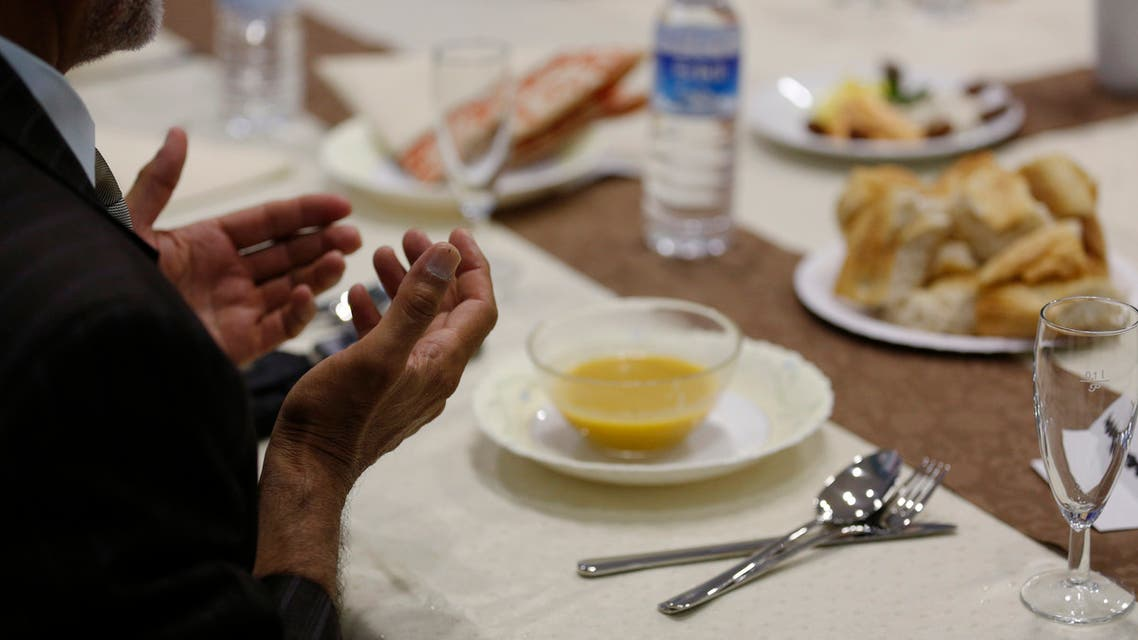 A Muslim man breaks his fast at a ceremony during the Muslim fasting month of Ramadan in Cologne. (Reuters)