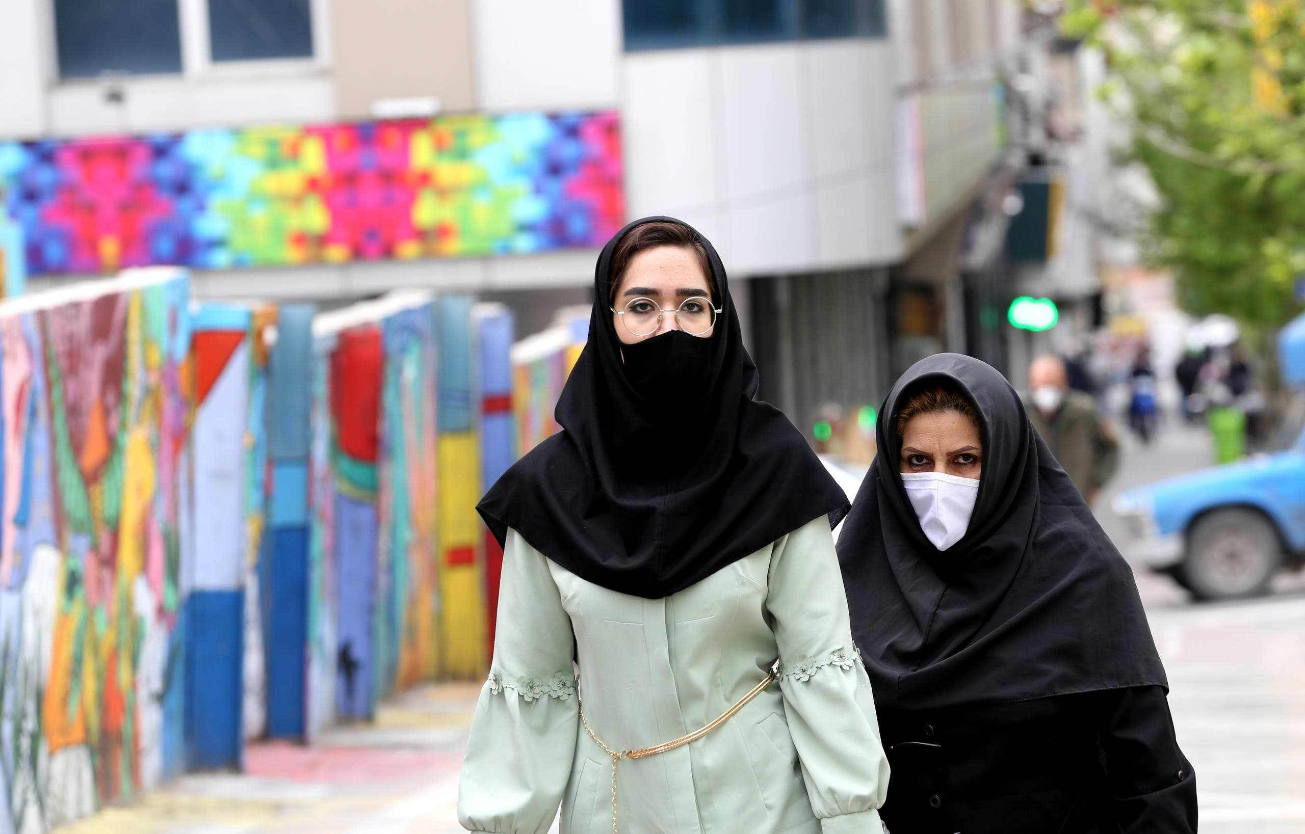 Iranians wearing protective mask walk past graffiti on a wall in Tehran on April 13, 2020 during the coronavirus COVID-19 pandemic. Iran's health ministry today reported another 111 deaths from the novel coronavirus, taking the official overall toll in the worst-hit Middle East country to 4,585. Ministry spokesman Kianoush Jahanpour said 1,617 new infections took the total number of cases in the country's outbreak to 73,303, of whom 45,983 had recovered.