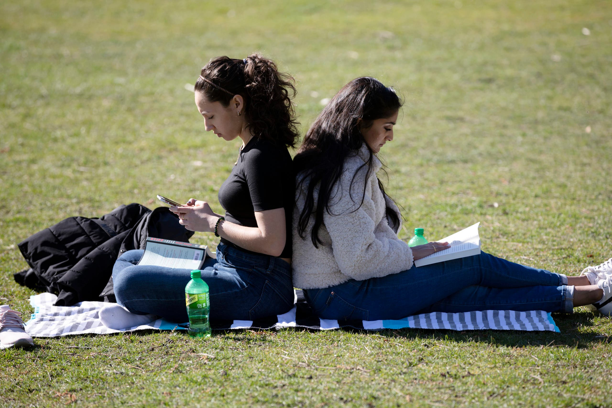 Letitia Klos, left, and her roommate Aesha Patel, both students at Boston University Dental School, spend time in The Public Garden in Boston, Friday, on March 27, 2020. (AP)