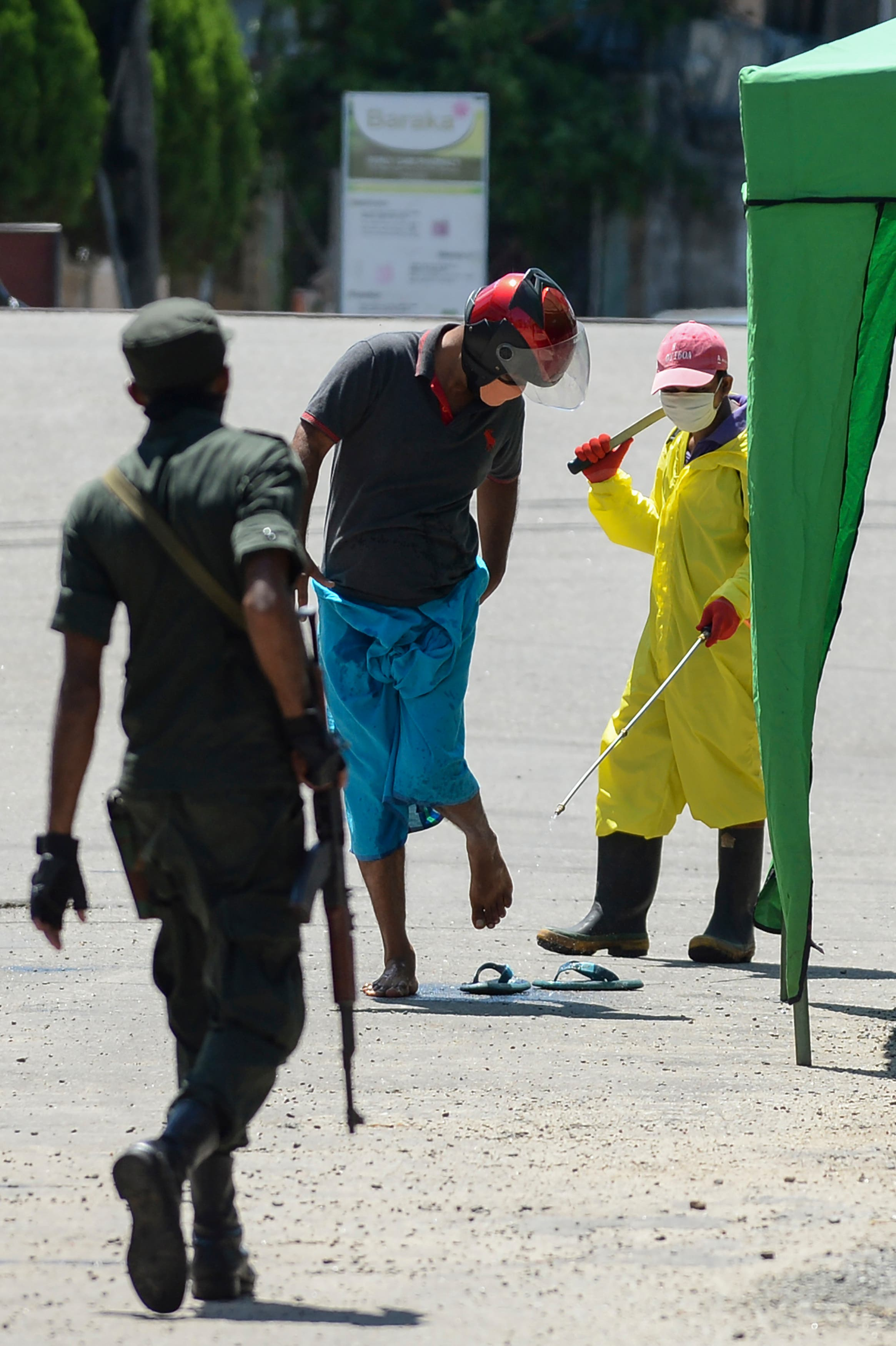 A municipal worker (R) sprays disinfectant solution on a man at a checkpoint during a government-imposed nationwide lockdown as a preventive measure against the spread of the COVID-19 coronavirus in Beruwala on April 16, 2020. (AFP)