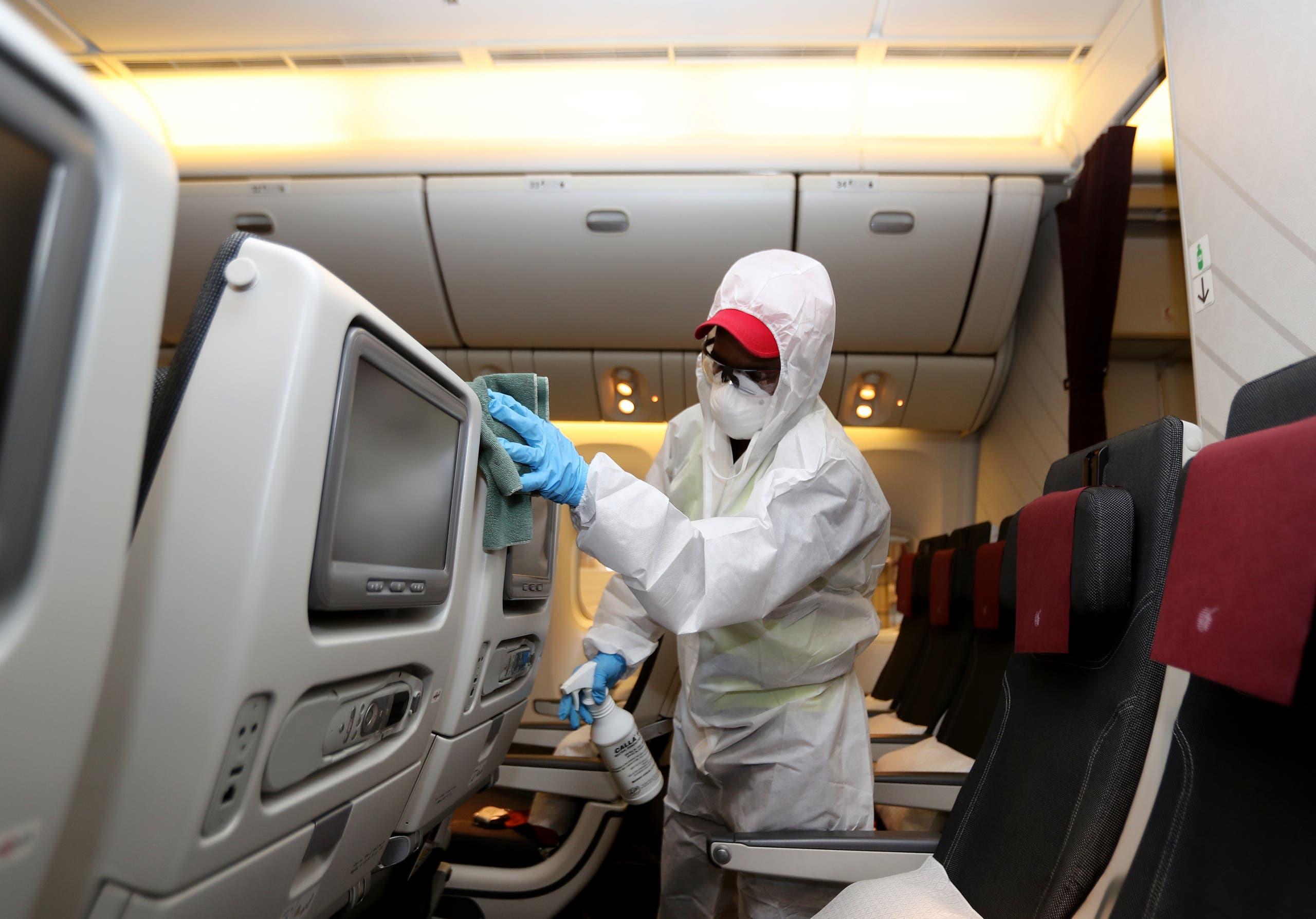 عامل يعقم طائرة مرتدياً لباساً واقياً في قطر