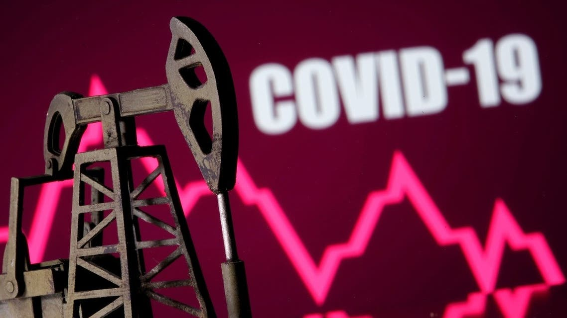 A 3D printed oil pump jack is seen in front of displayed stock graph and COVID-19 words in this illustration picture. (Reuters)