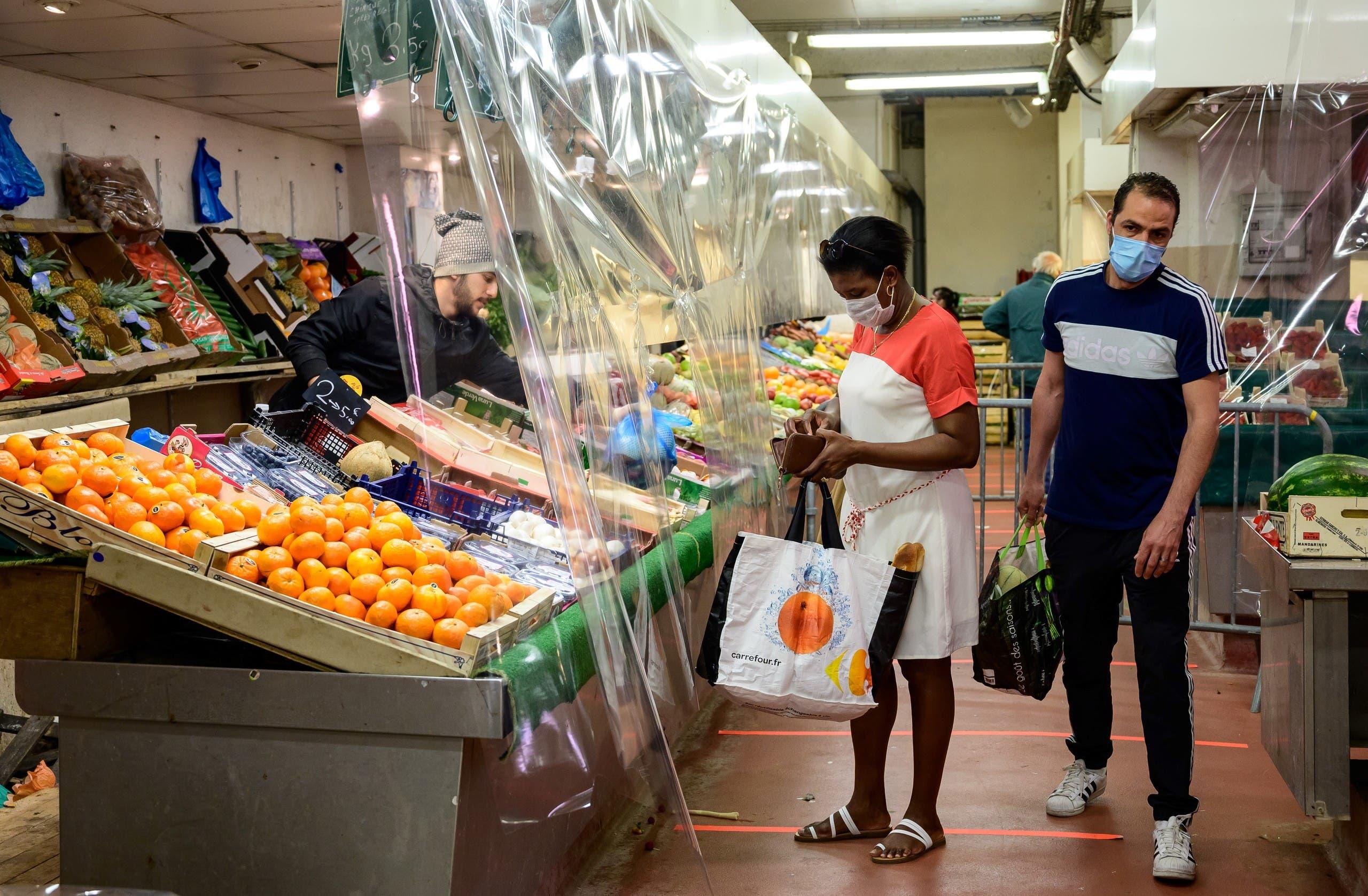 أشخاص بسوق الخضر يضعون كمامات للوقاية من كورونا