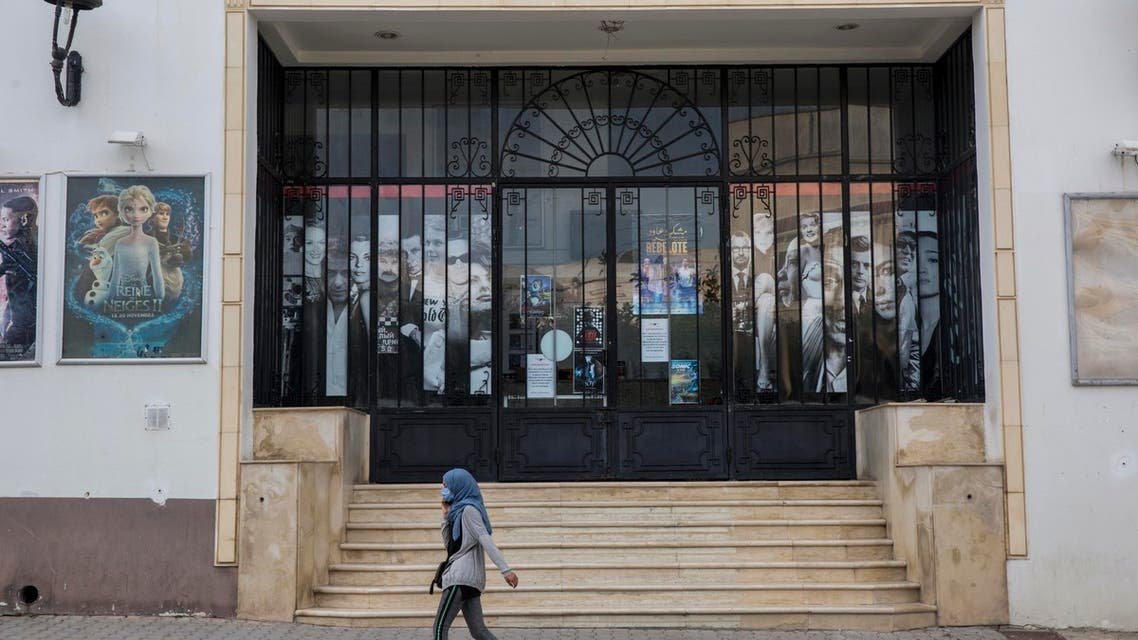 A woman wearing a mask walks past a closes movie theater during the coronavirus outbreak, in La Marsa outside Tunis, Tunisia. (AP)