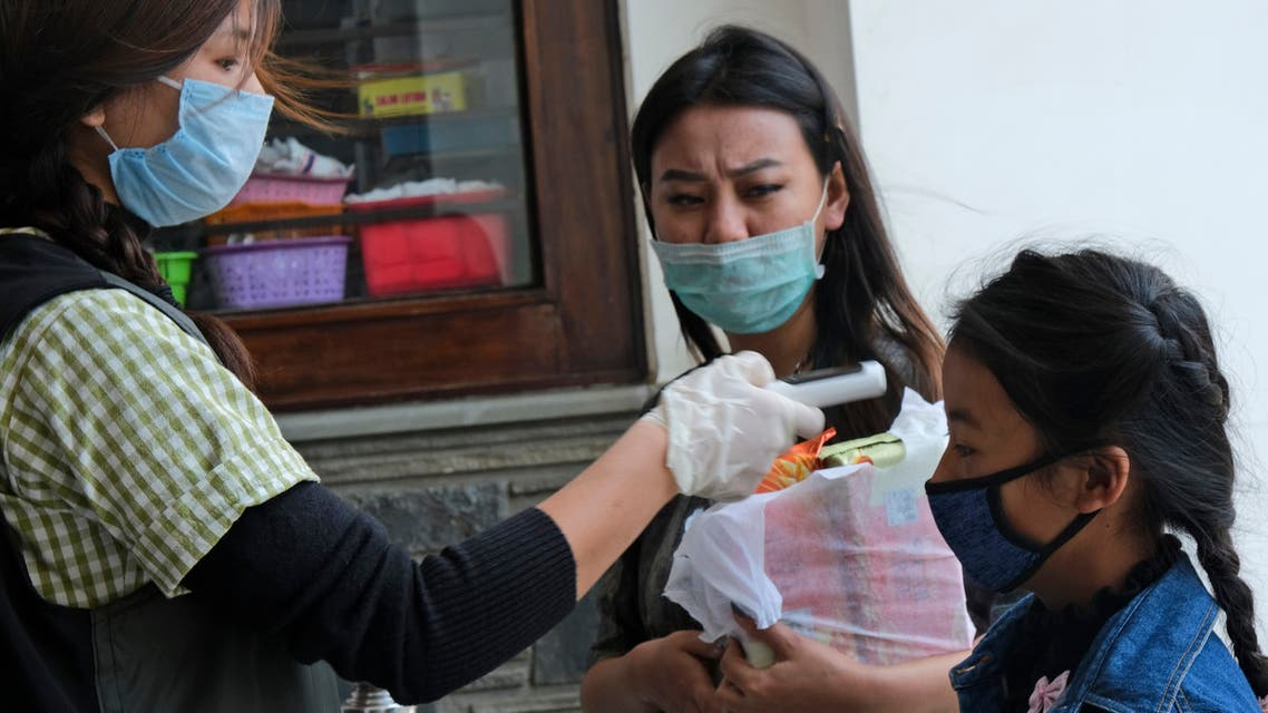A medical staff checks the temperature of a girl at the entrance of Oking Hospital in Kohima, capital of the northeastern Indian state of Nagaland, Monday, April 13, 2020 (AP)