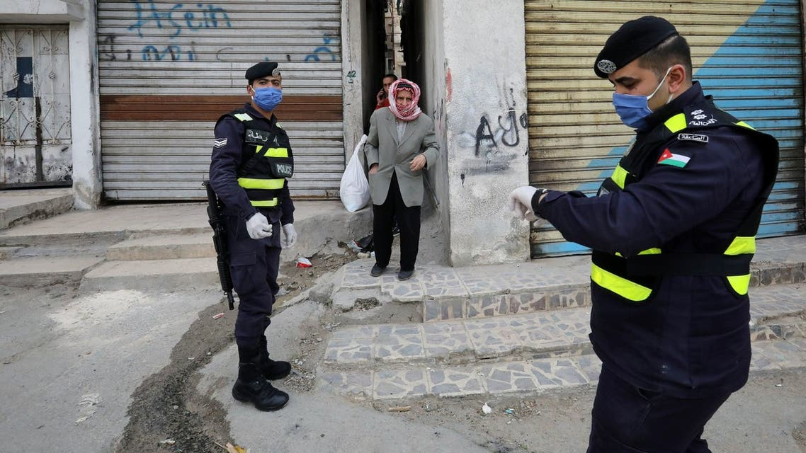 Jordanian police officers stand guard as a man waits to get bread in a closed-down part of Al-Nasr area, amid the coronavirus disease (COVID-19) outbreak, in Amman, Jordan, April 15, 2020. REUTERS/Muhammad Hamed