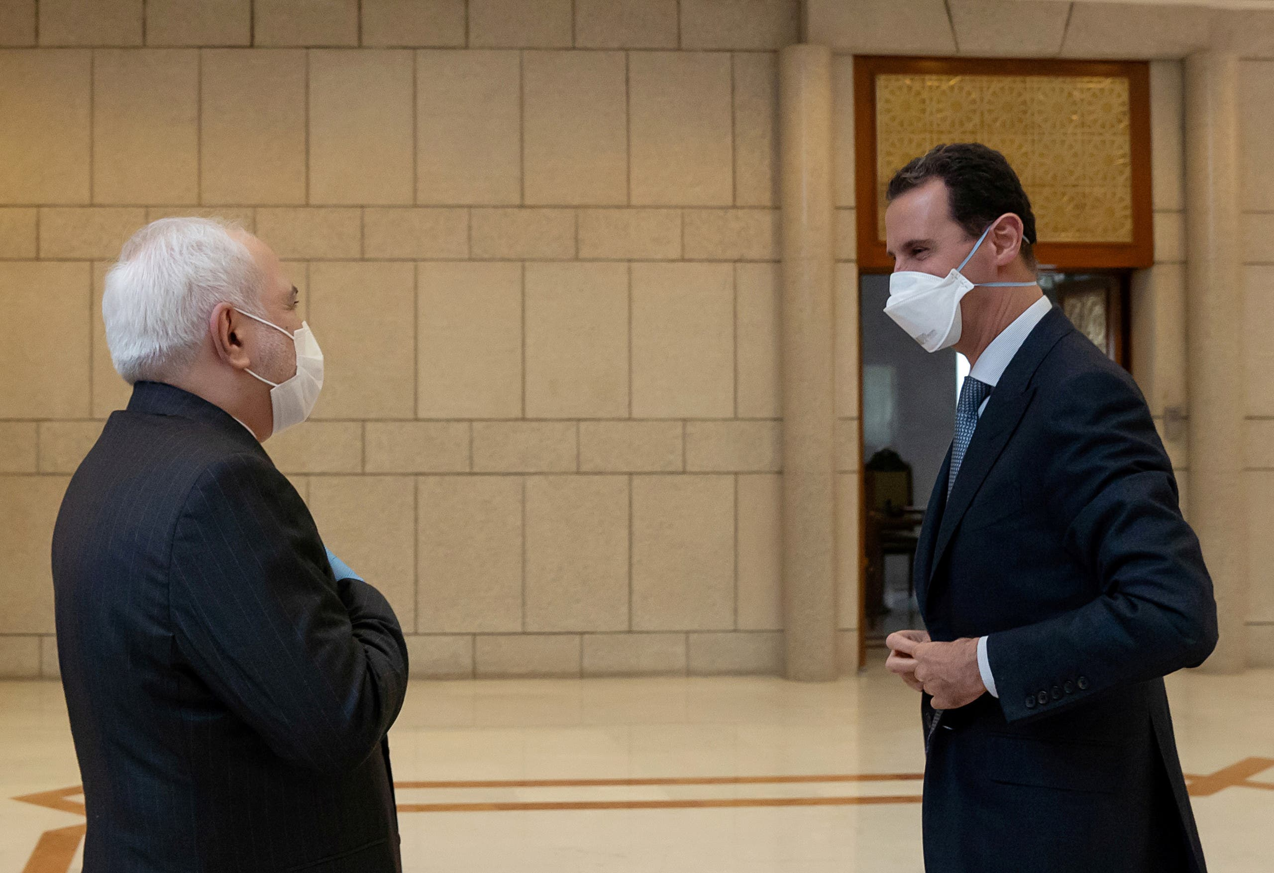 Syria's President Bashar al-Assad and Iran's Foreign Minister Mohammad Javad Zarif, wearing face masks as protection against the spread of the coronavirus disease (COVID-19), meet in Damascus, Syria. (Reuters)