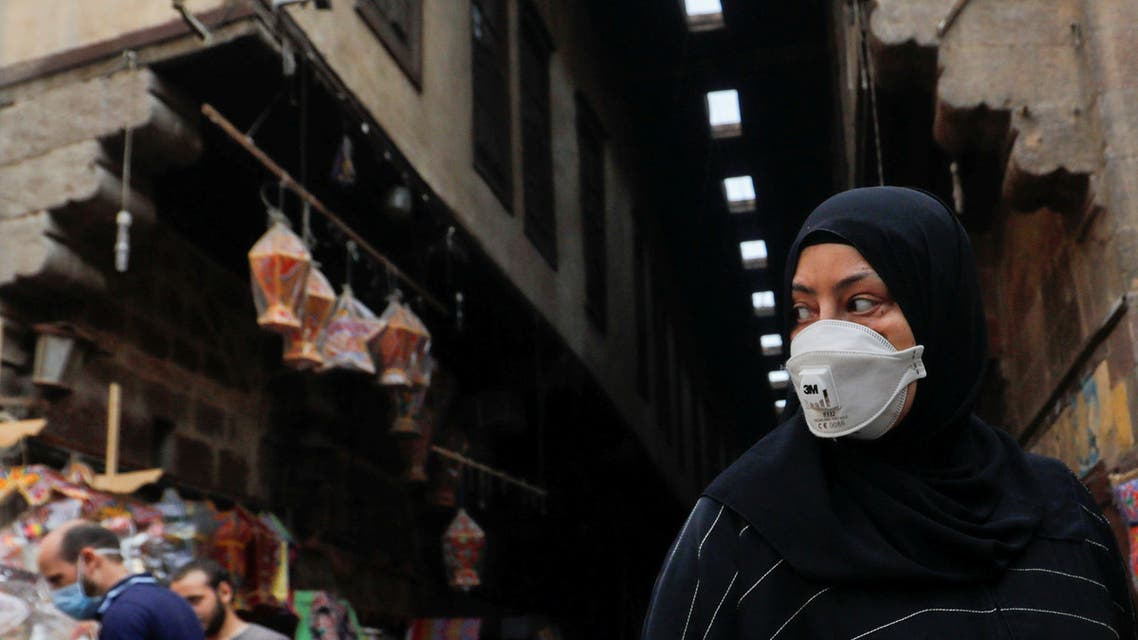 FILE PHOTO: A woman wearing a protective face mask, amid concerns over the coronavirus disease (COVID-19), looks at traditional Ramadan lanterns, called Fanous which are displayed for sale at a stall, ahead of the Muslim holy month of Ramadan at Al Khayamia street in old Cairo, Egypt April 16, 2020. REUTERS/Amr Abdallah Dalsh/File Photo