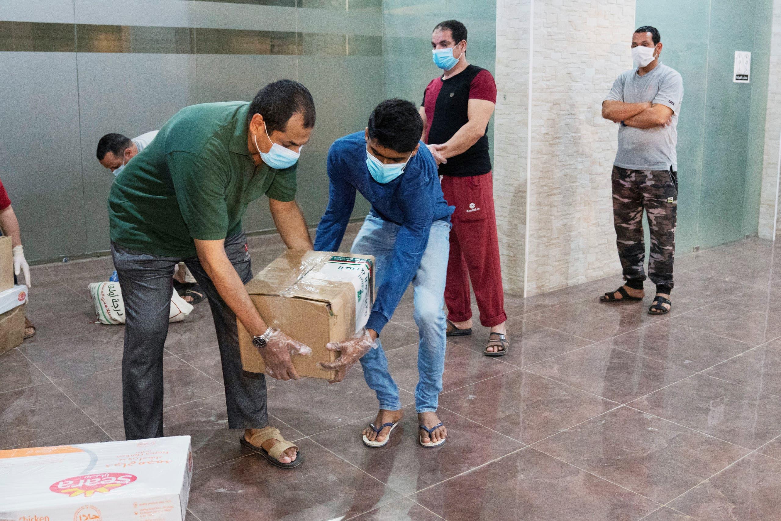 عمال أجانب يتسلمون مساعدات في الكويت