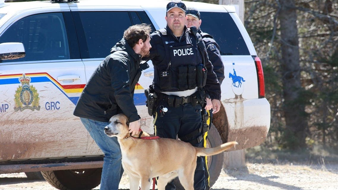 RCMP officer Cedric Landry releases a dog to a man at the checkpoint onto Portapique Beach Road after Gabriel Wortman, a suspected shooter, was taken into custody in Portapique, Nova Scotia, Canada. (Reuters)