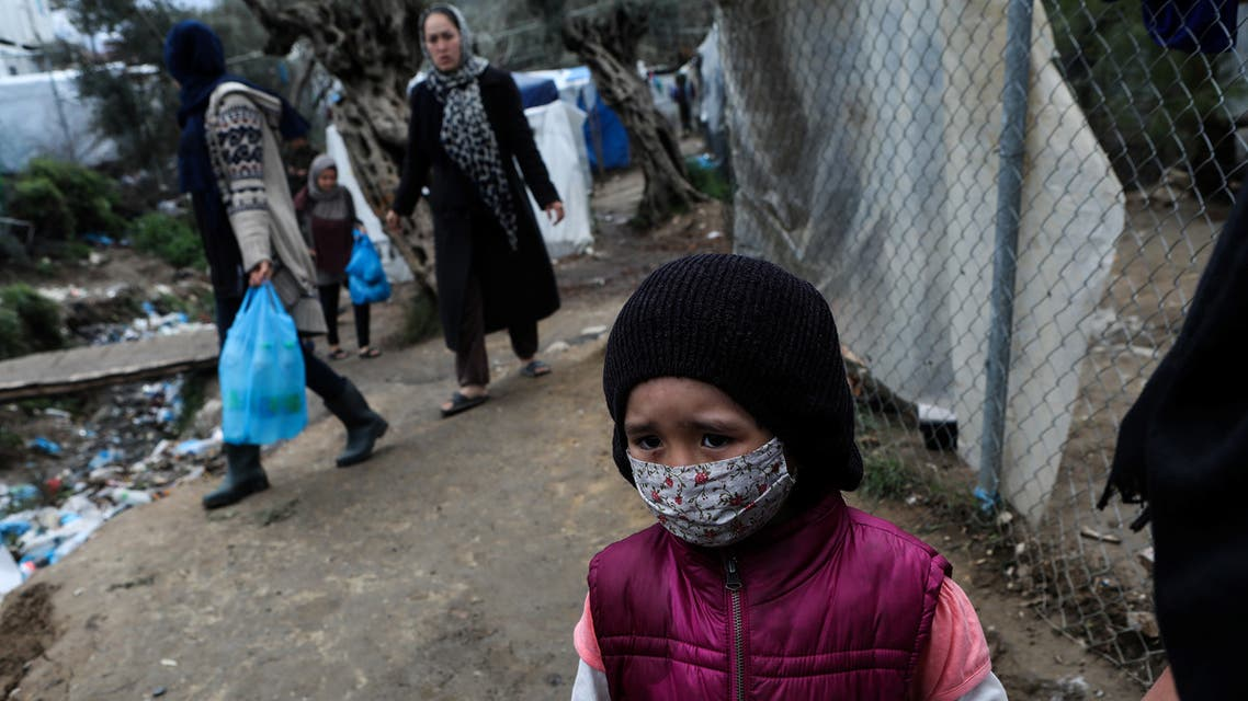 A girl wears a protective face mask at a makeshift camp for refugees and migrants next to the Moria camp, during a nationwide lockdown to contain the spread of the coronavirus disease (COVID-19), on the island of Lesbos, Greece April 02, 2020. REUTERS/Elias Marcou