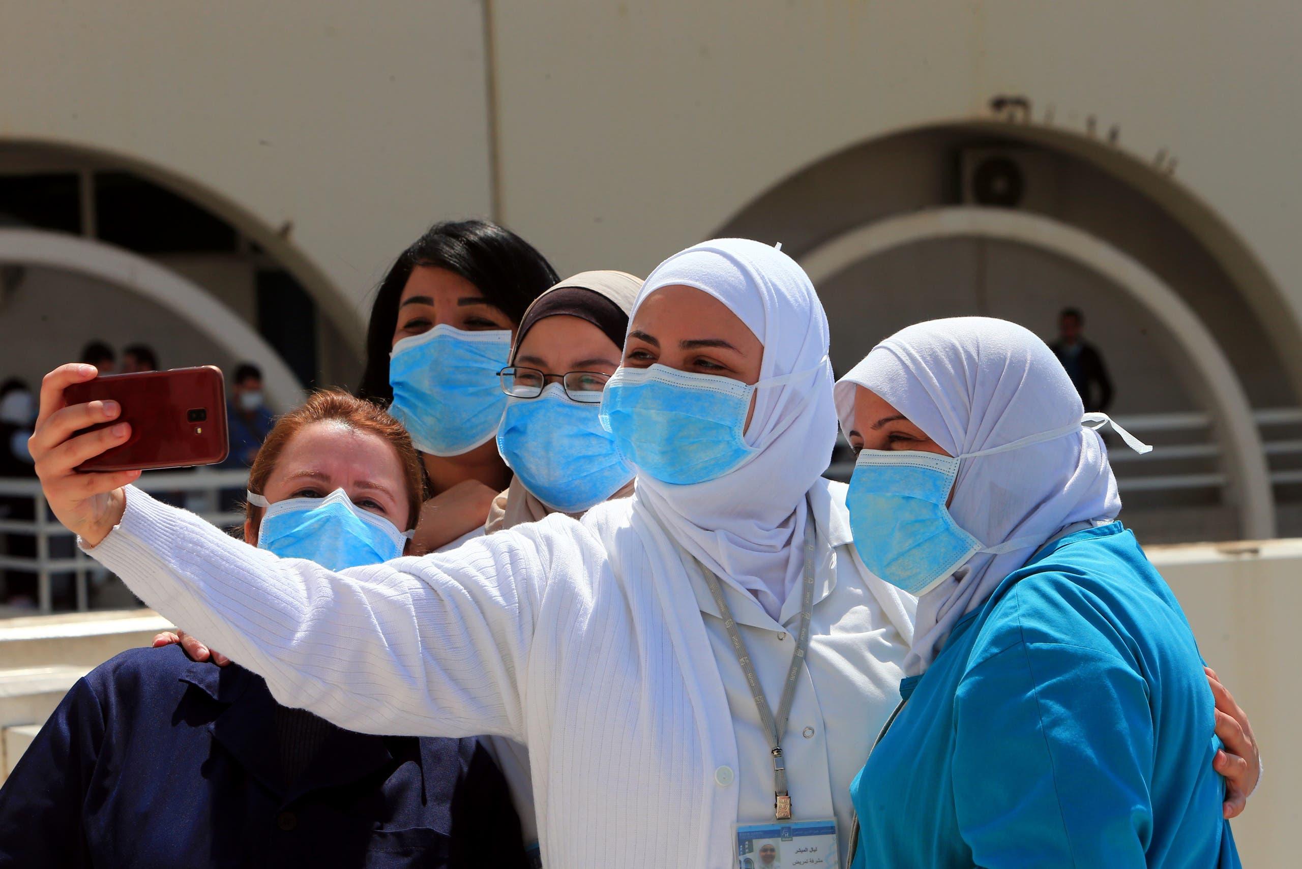 عاملات صحة يأخذن صورة تذكارية خلال حفل موسيقي صغير أقيم قرب مستشفى ببيروت حيث يعالج مرضى كورونا