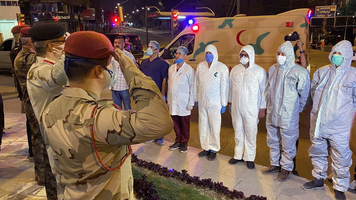 Iraqi Army officers salot to a group of doctors and midecal staff in solidarity with the families of those who have died or are ill with the coronavirus and support for doctors and nurses fighting to save them, in central Baghdad, Iraq on April 7, 2020. (AP)