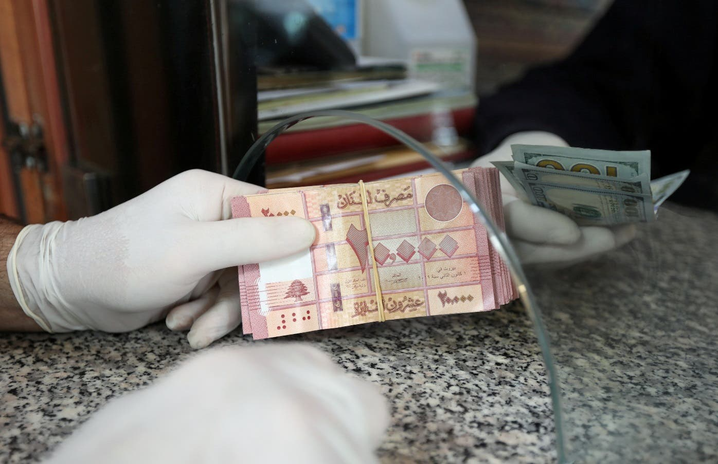 A customer wearing gloves holds Lebanese pounds at a currency exchange store in Beirut, Lebanon April 3, 2020. (Reuters)