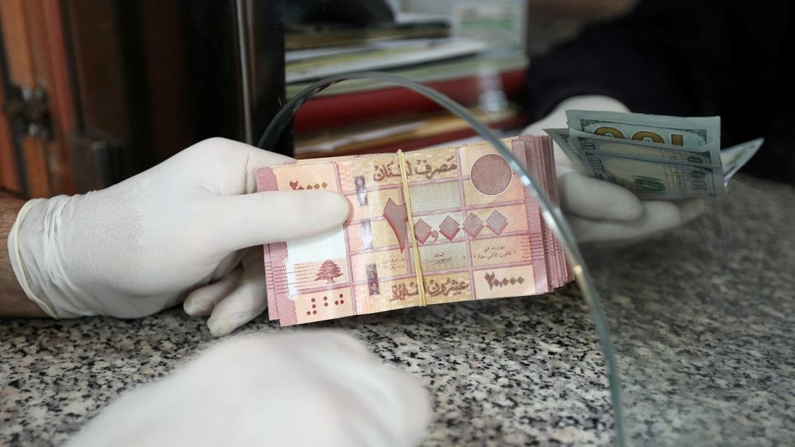 A customer wearing gloves holds Lebanese pounds at a currency exchange store, during a countrywide lockdown to combat the spread of coronavirus disease (COVID-19) in Beirut, Lebanon April 3, 2020. (Reuters)
