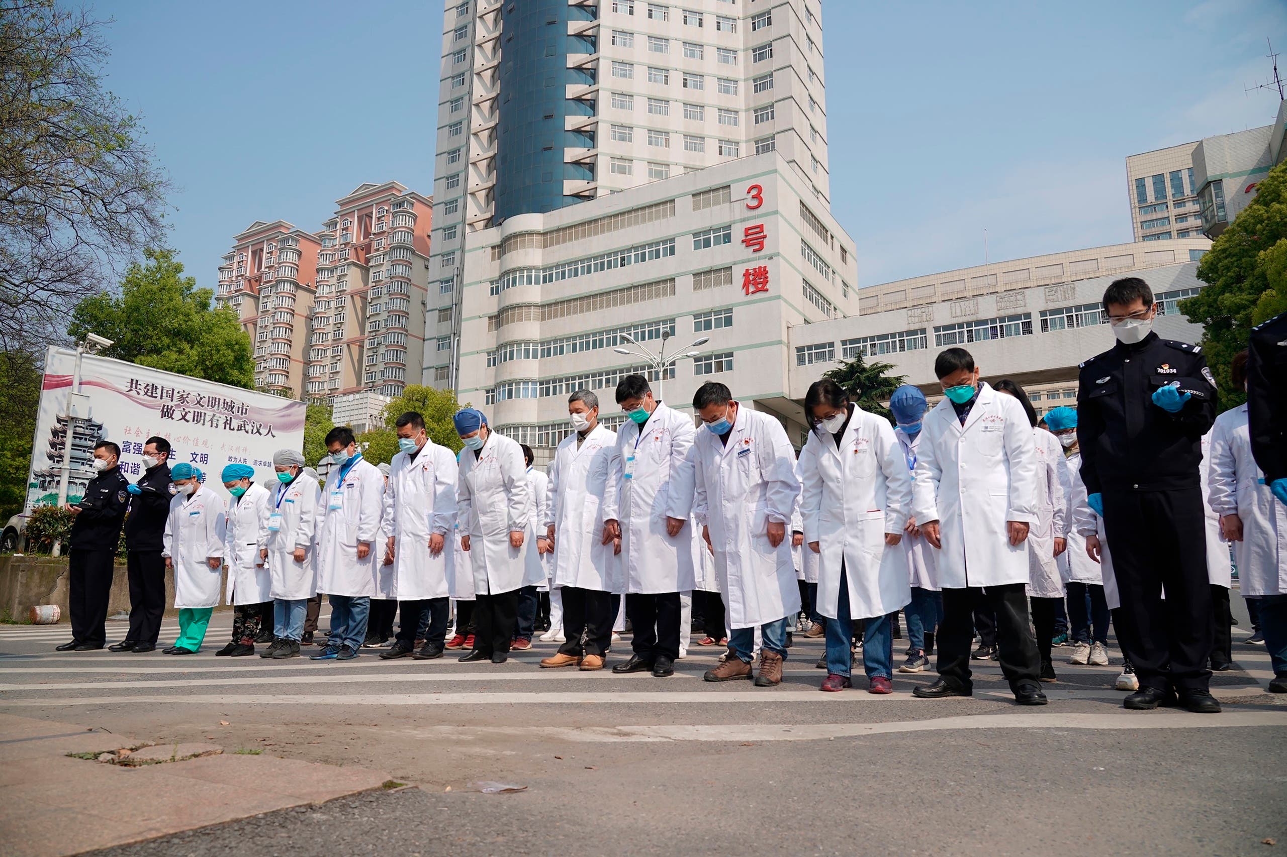 Medical workers bow their heads during a national moment of mourning for victims of coronavirus in Wuhan in central China's Hubei Province on April 4, 2020. (AP)