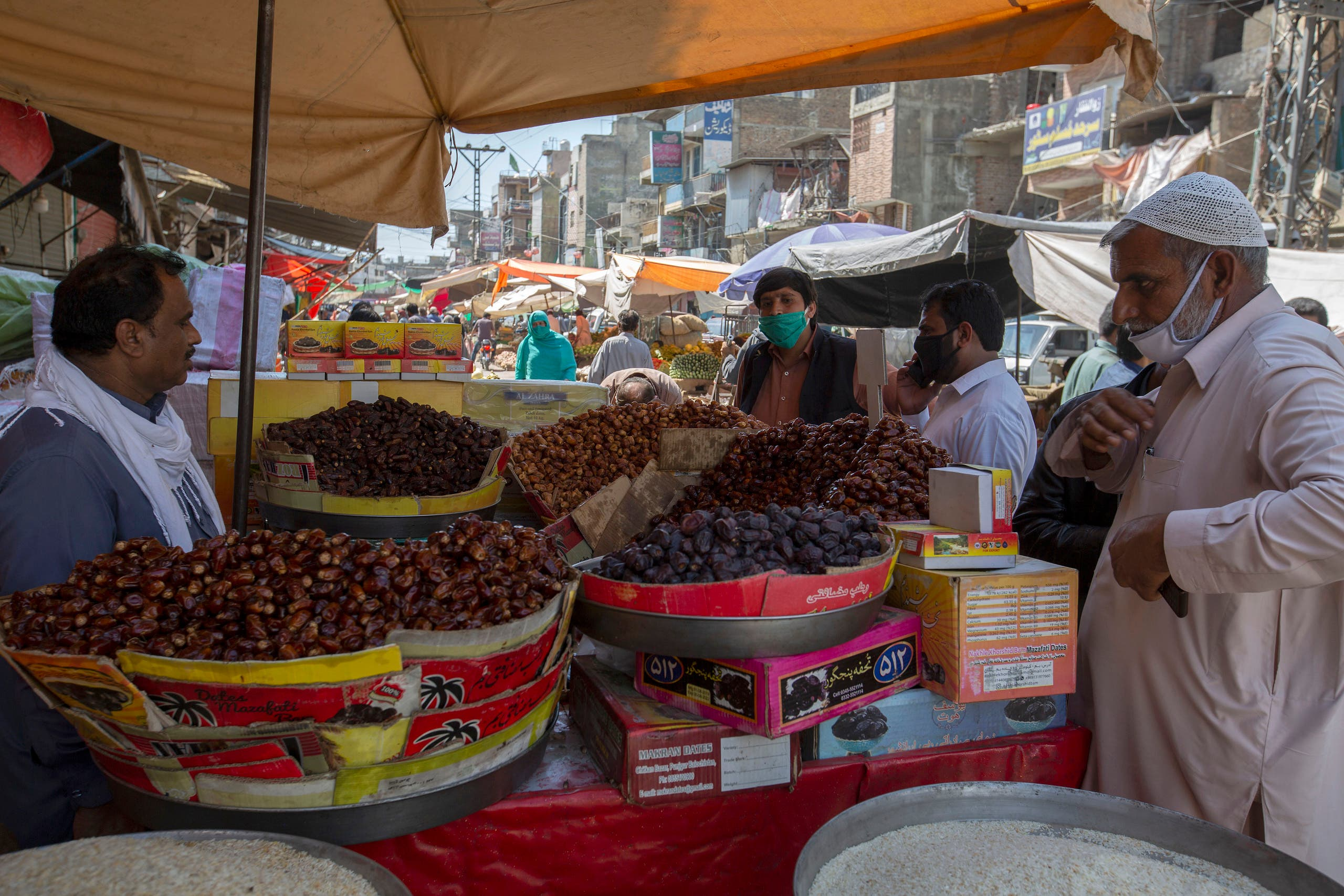 Consumers buy dates for the upcoming fasting month of Ramadan, during a lockdown to contain the spread of coronavirus, in Rawalpindi, Pakistan, on Tuesday, April 21, 2020. (AP)