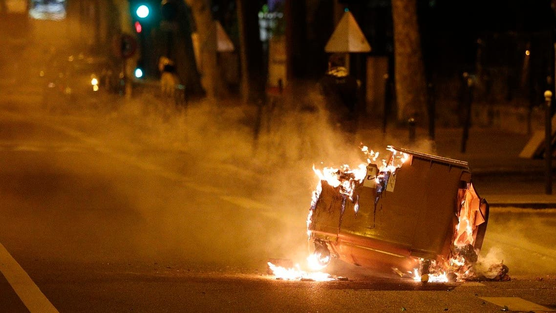 A trash bin burns in the street during clashes in Villeneuve-la-Garenne, in the northern suburbs of Paris, early on April 21, 2020. (AFP)