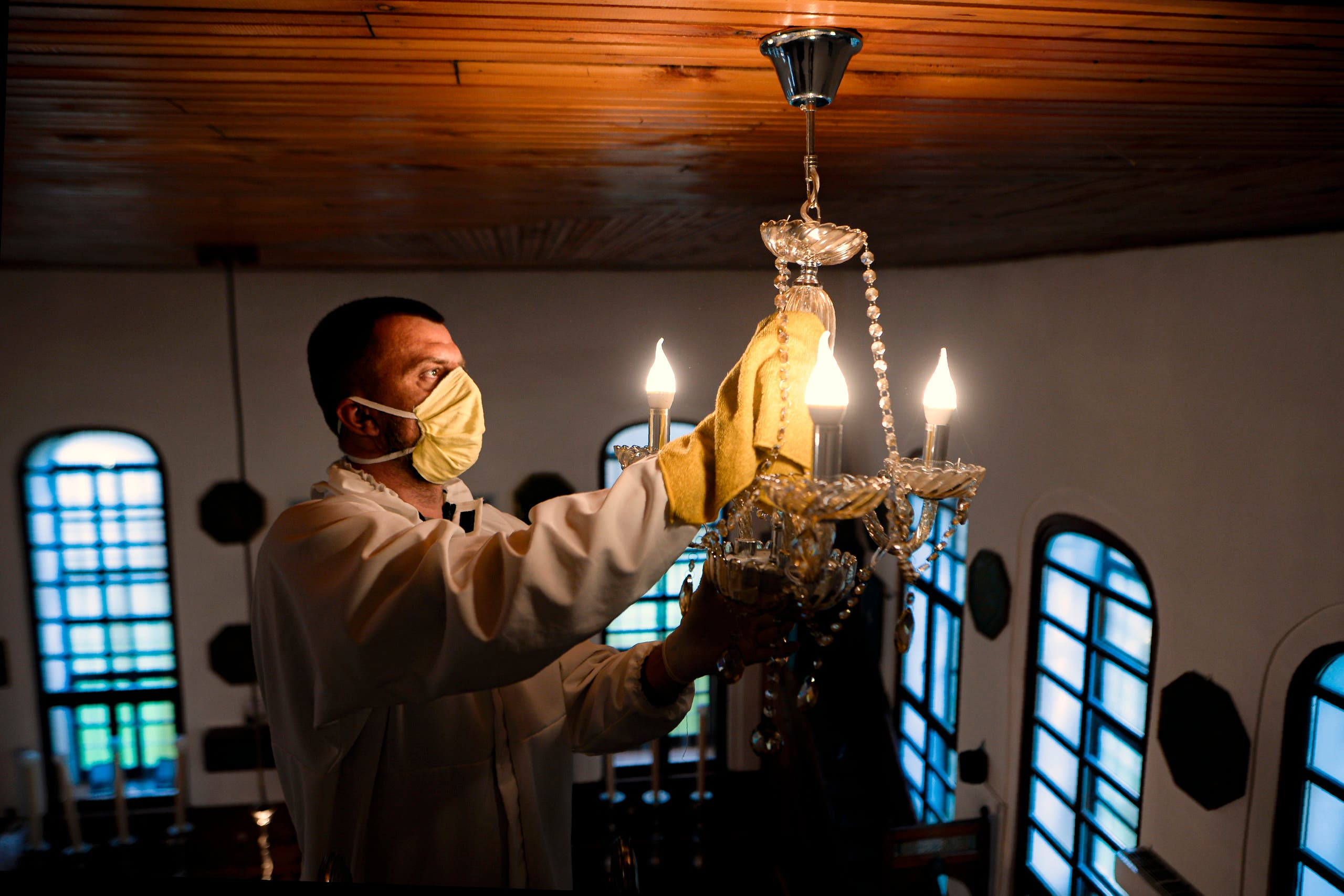 A man disinfects the ceiling lamp in the Cobanija mosque in Sarajevo, Bosnia, on Tuesday, April 21, 2020.  (AP)