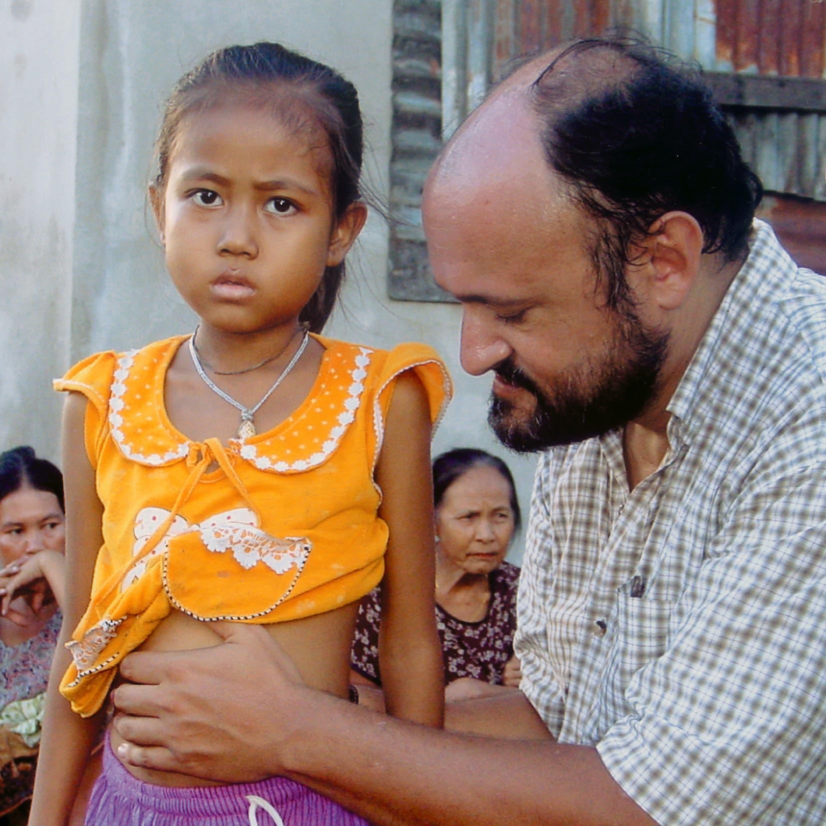أورباني مع أحد الأطفال بدول شرق آسيا