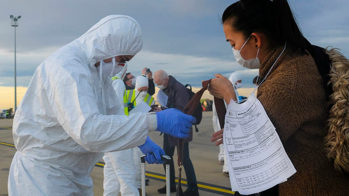 A worker wearing a protective suit checks the luggage of an evacuee from Wuhan, China, after their evacuation flight landed at an airport in Marseilles, France on Feb. 2, 2020. (AP)