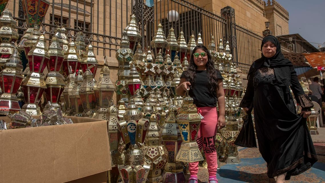 A girl poses for a photograph with a lantern she just bought with her mother as a woman makes her way through a market, in the Sayeda Zeinab neighborhood of Cairo, Egypt, Tuesday, April 21, 2020.  (AP)