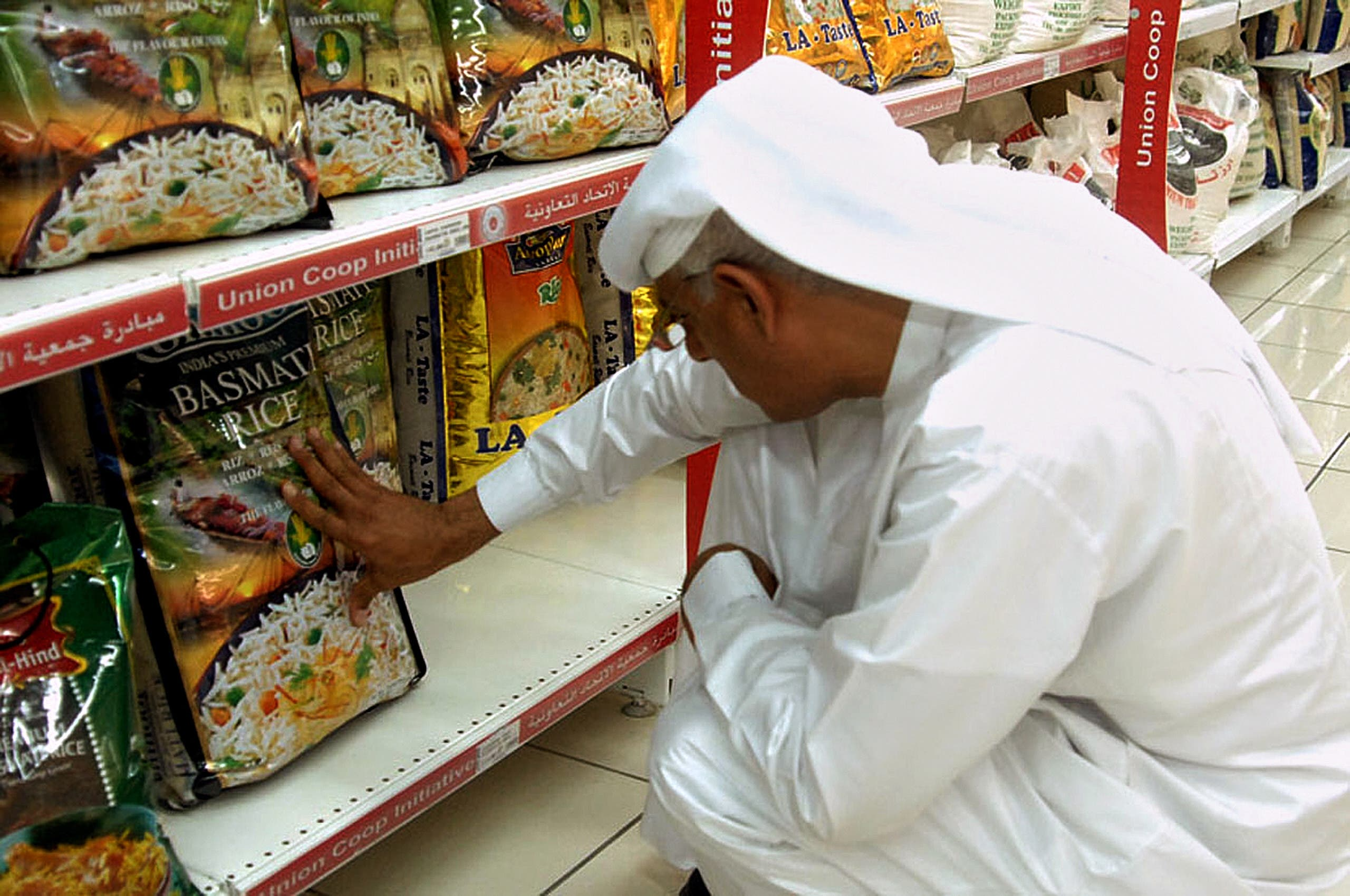 An Emirati man reads the front of a package of Indian Basmati rice in a supermarket in Dubai on July 19, 2008. (File photo: AFP)
