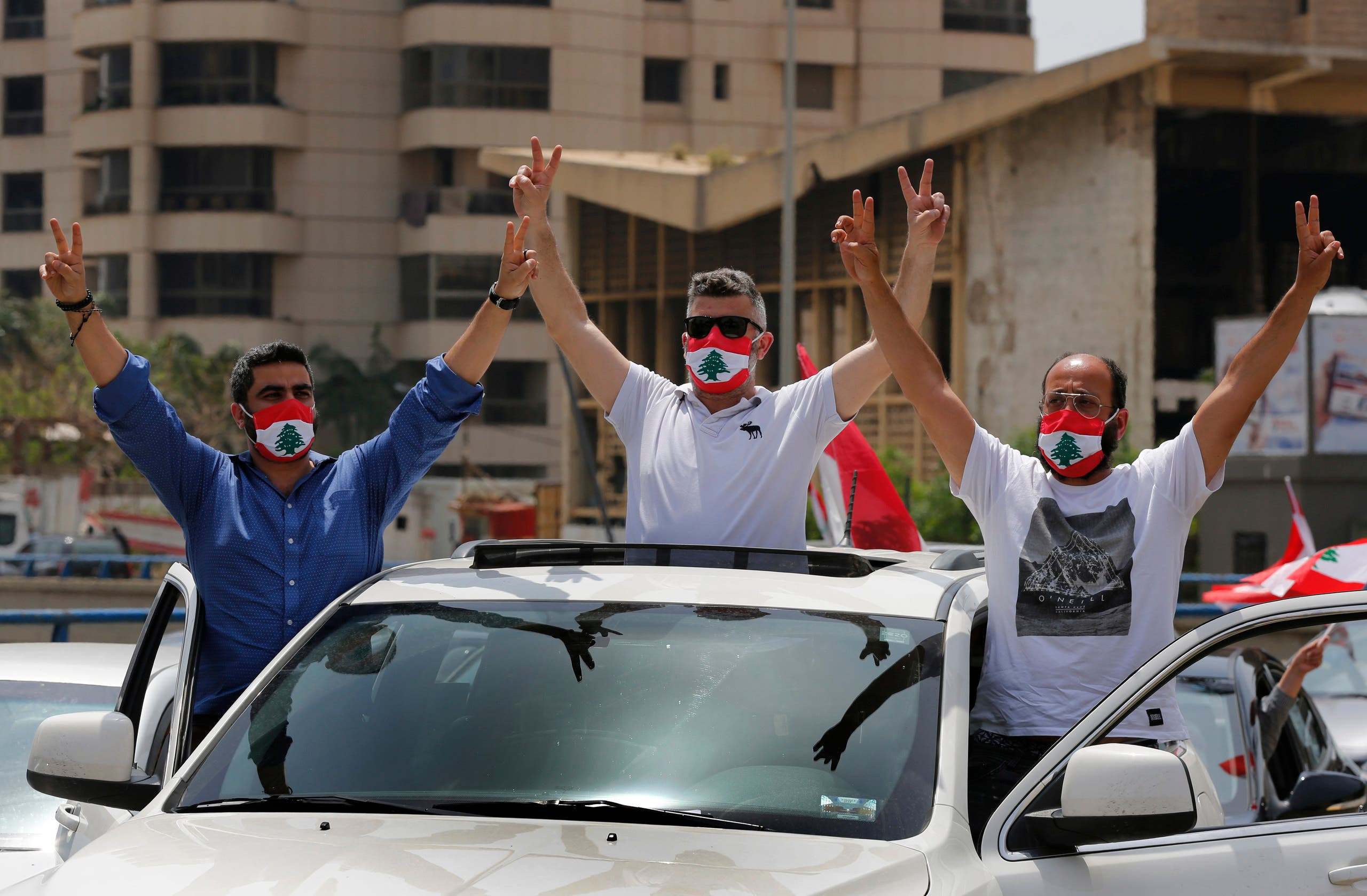 Anti-government protesters flash the victory sign during a driving convoy protest through the streets to express rejection of the political leadership they blame for the economic and financial crisis, in Beirut, Lebanon, on Tuesday, April 21, 2020. (AP)