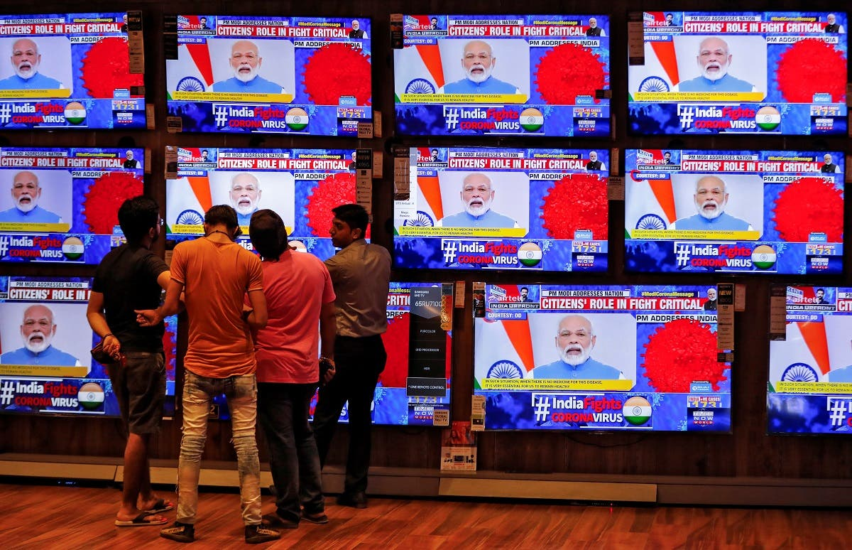 People watch Indian Prime Minister Narendra Modi addressing the nation amid concerns about the spread of coronavirus disease, on TV screens inside a showroom in Ahmedabad, India, on March 19, 2020. (Reuters)