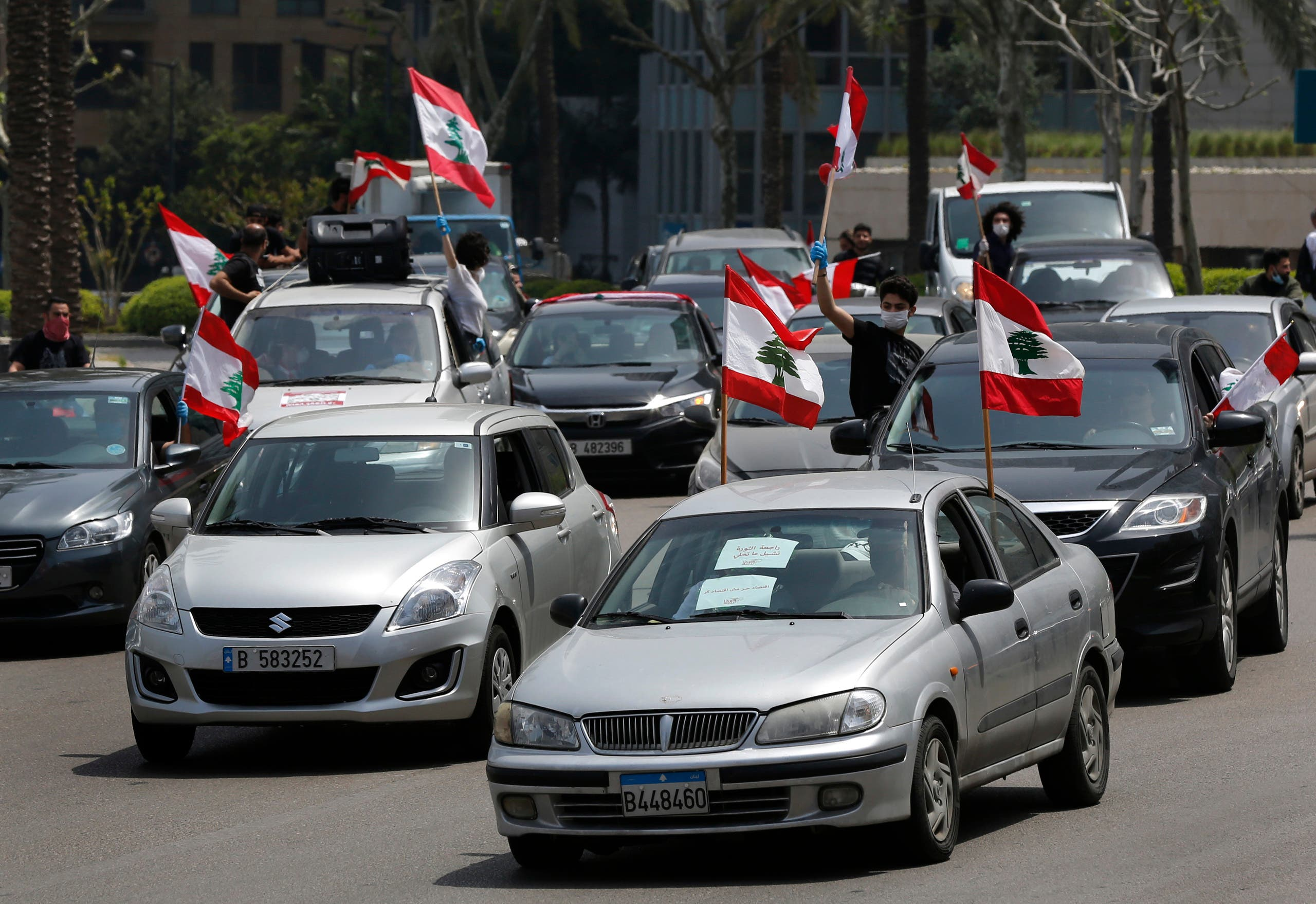 Anti-government protesters wave Lebanese flags from their cars as they protest by driving through the streets, in Beirut, Lebanon, on Tuesday, April 21, 2020. (AP)