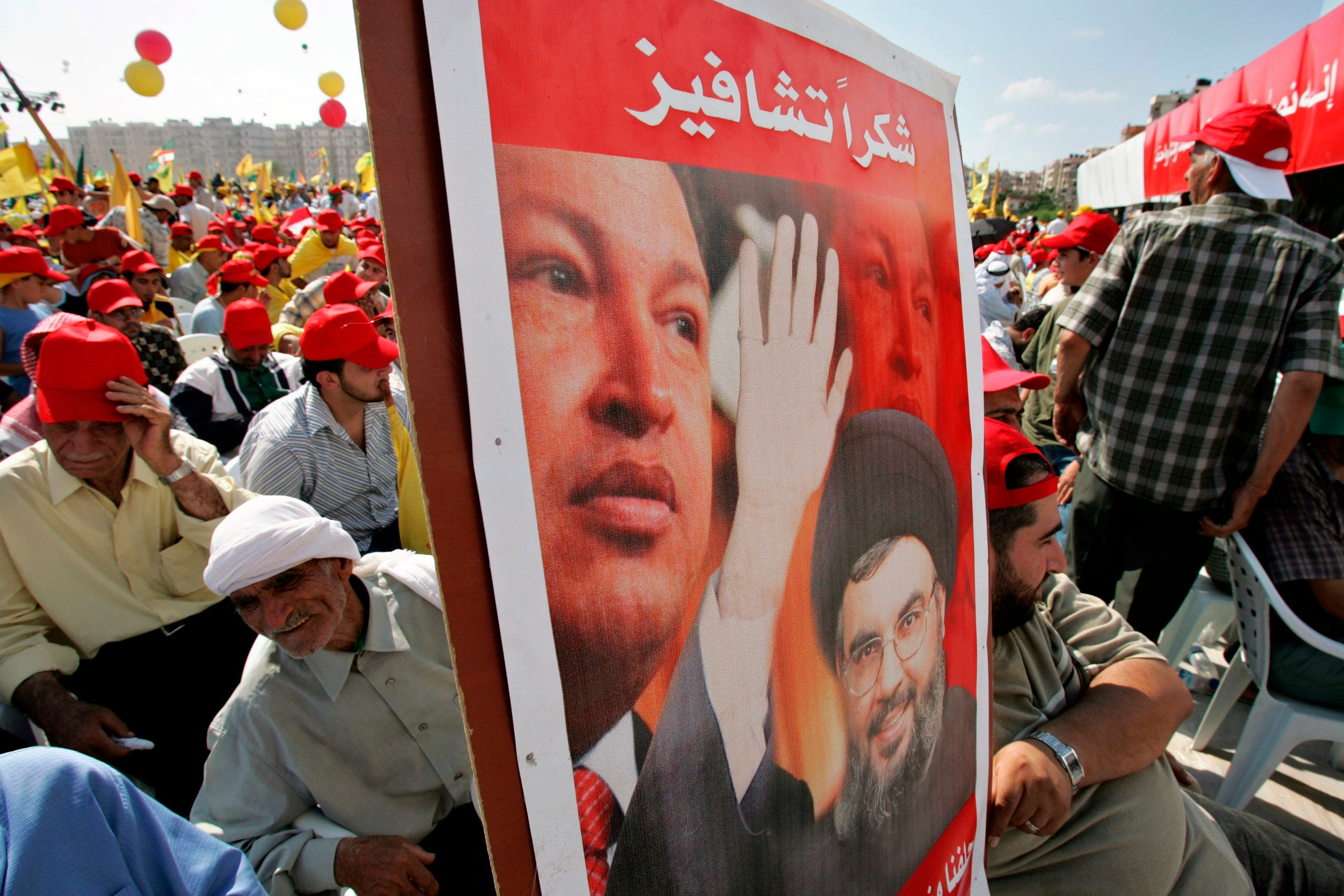 Hezbollah supporters carry a banner showing Hezbollah leader Hassan Nasrallah and Venezuela's then-President Hugo Chavez in Beirut's suburbs on Sept. 22, 2006. (AP)