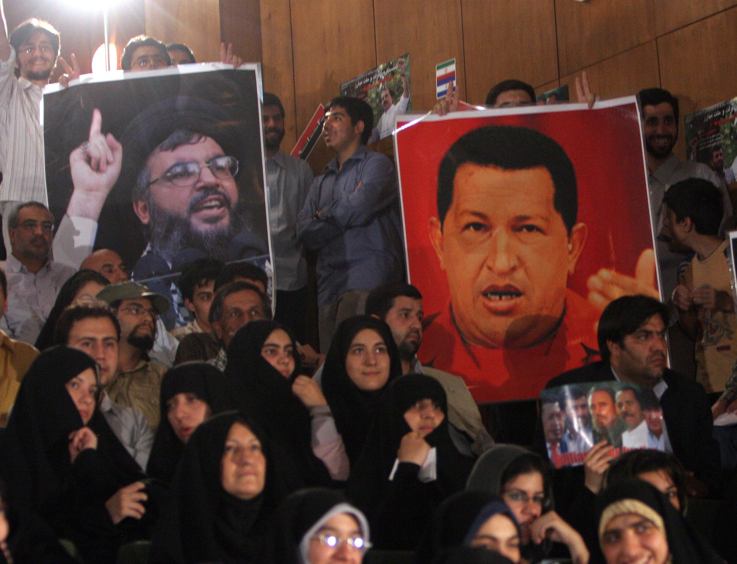 Iranian students hold a poster of Lebanese Hassan Nasrallah, the secretary general of Hezbollah, left, and Venezuela's then-President Hugo Chavez at Tehran University in Iran. (File photo: AP)