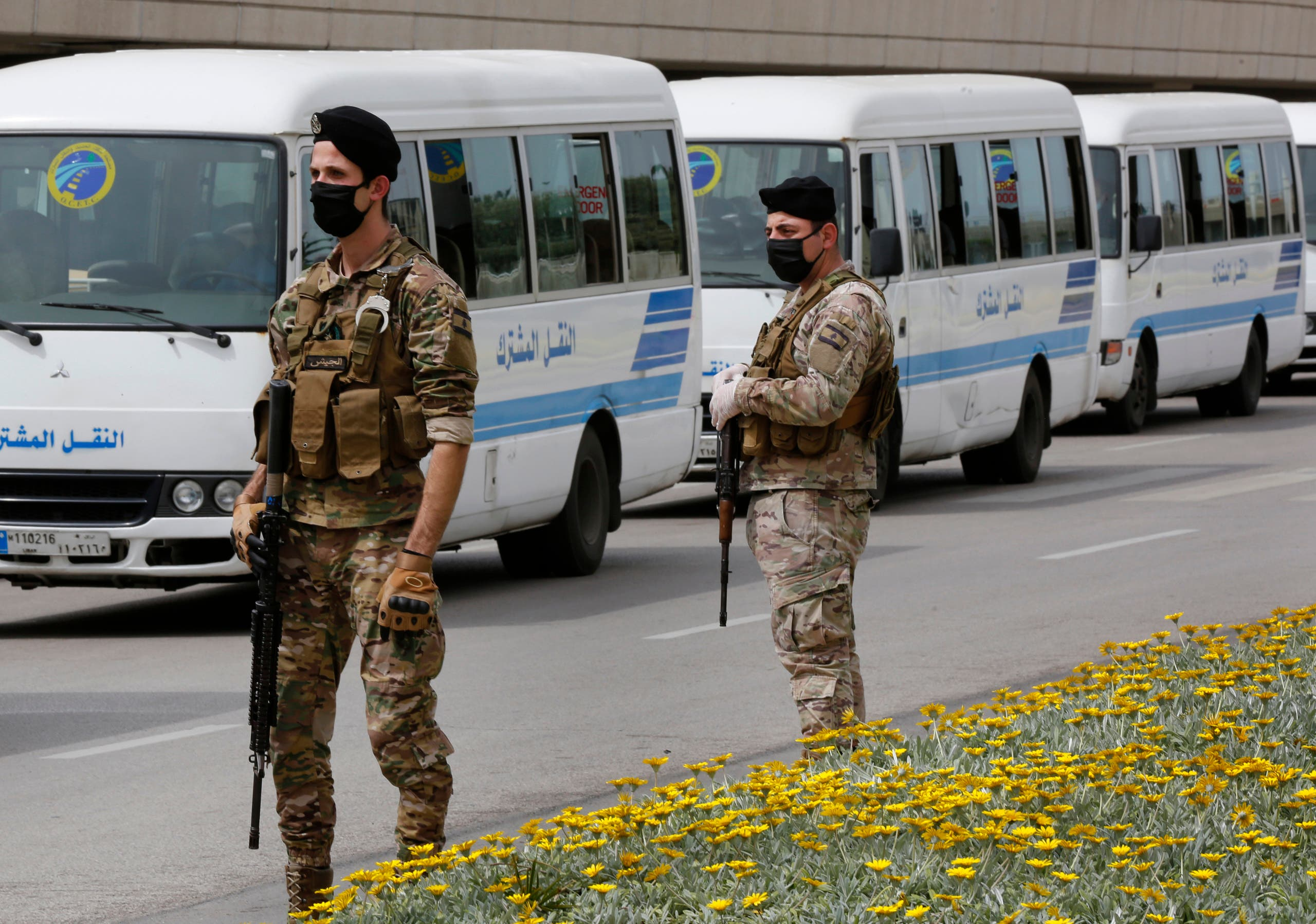 Lebanese army soldiers stand guard next to buses that will carry Lebanese passengers who were stuck in Saudi Arabia, at Rafik Hariri Airport, in Beirut on April 5, 2020. (AP)
