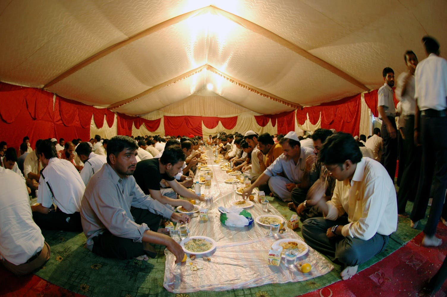Muslim labourers and workers prepare to break their fast during Ramadan in a charity tent set up to offer free iftar meals to poor working labourers in one of the residential areas in Dubai, UAE. (File photo: Reuters)