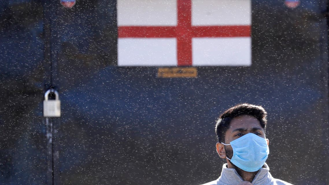 A man wears a protective face mask as he stands in front of a closed souvenir booth in Westminster in London, as the country is in lockdown to help curb the spread of coronavirus on April 21, 2020. (AP)