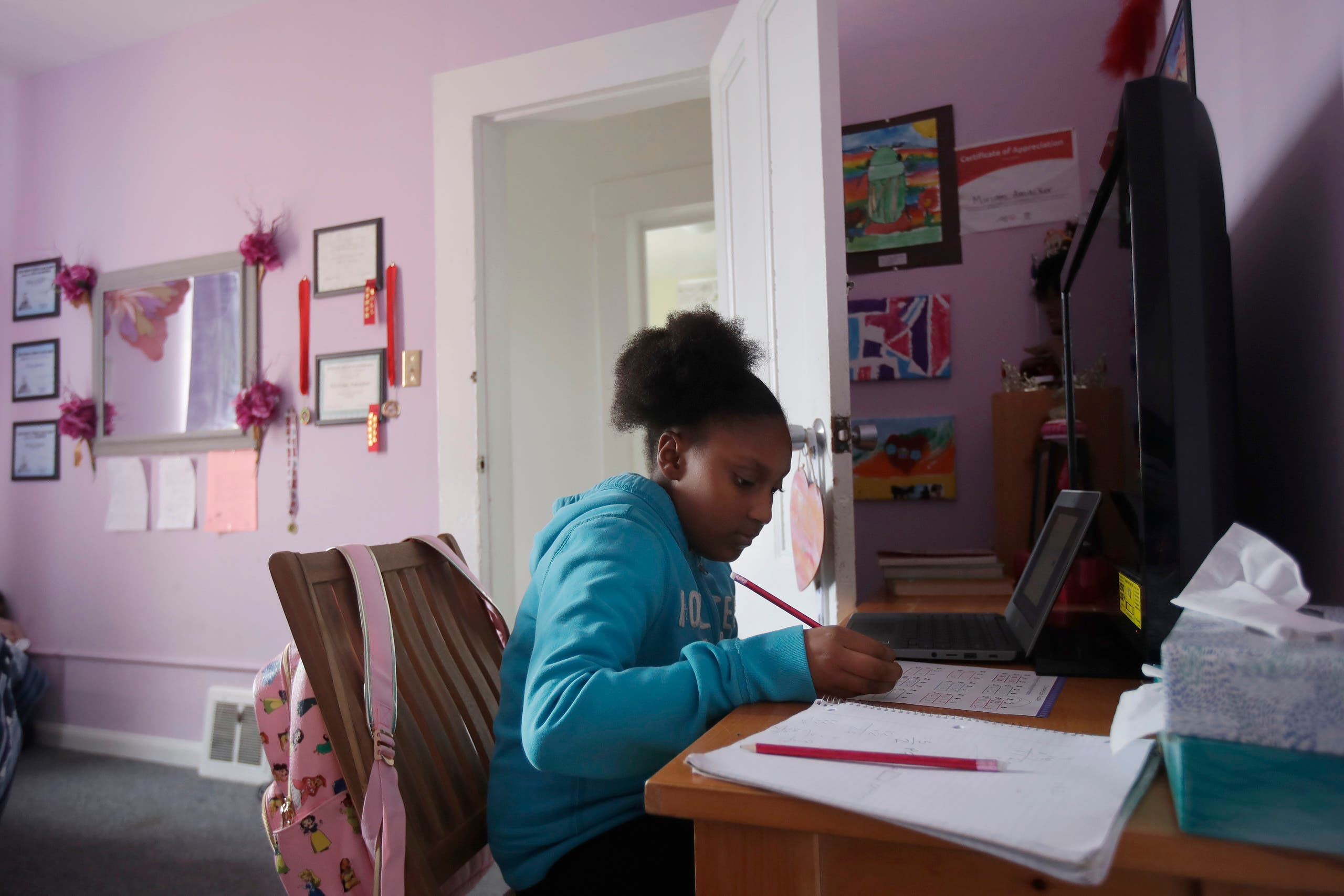 Elementary school fourth-grader Miriam Amacker does school work in her room at her family's home in San Francisco on April 9, 2020. (AP)