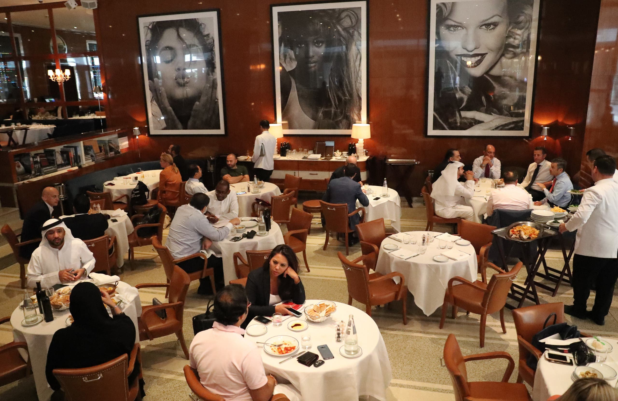 Peope eat at a restaurant in Dubai on August 30, 2018. (AFP)