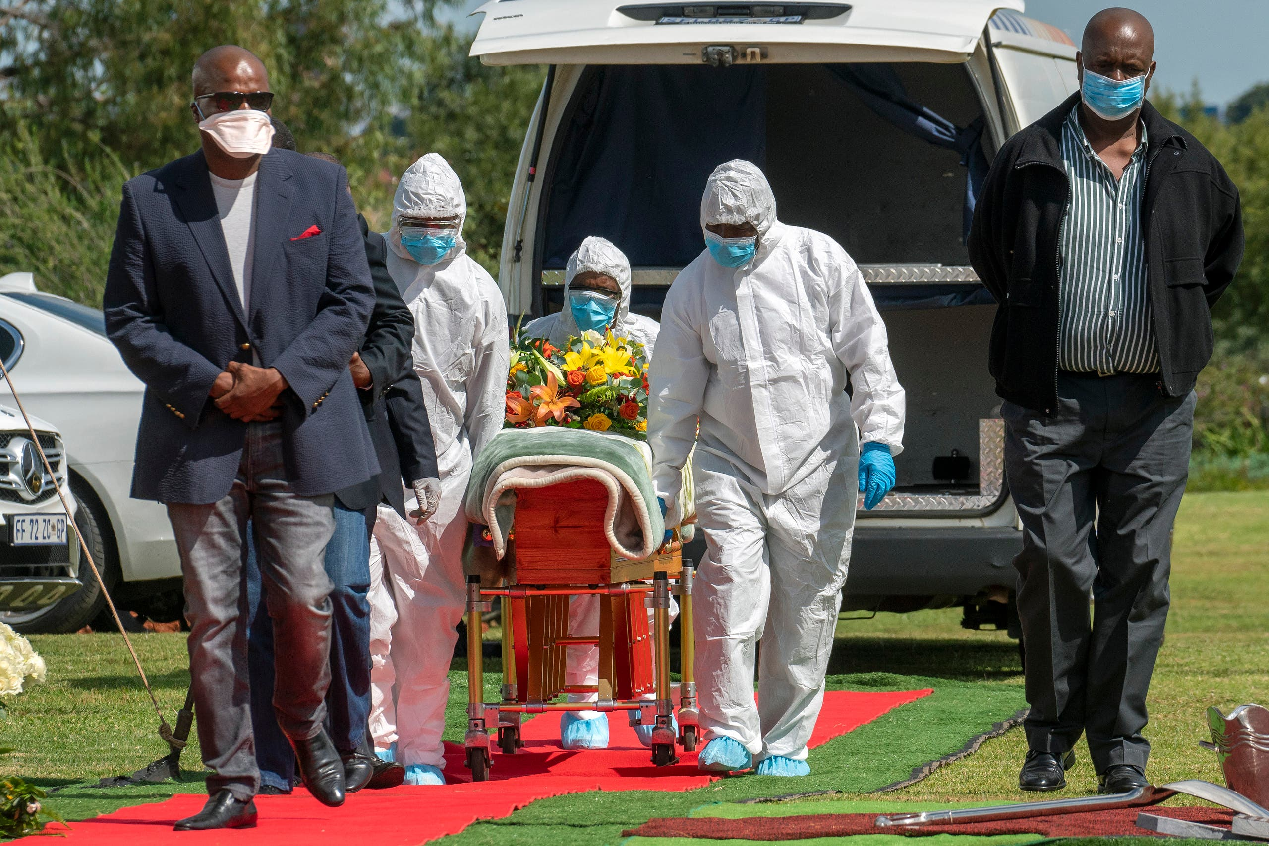 Pallbearers wearing personal protective equipment suits lift the casket containing the remains of a victim of COVID-19 outside Johannesburg, South Africa, on April 16, 2020. (AP)