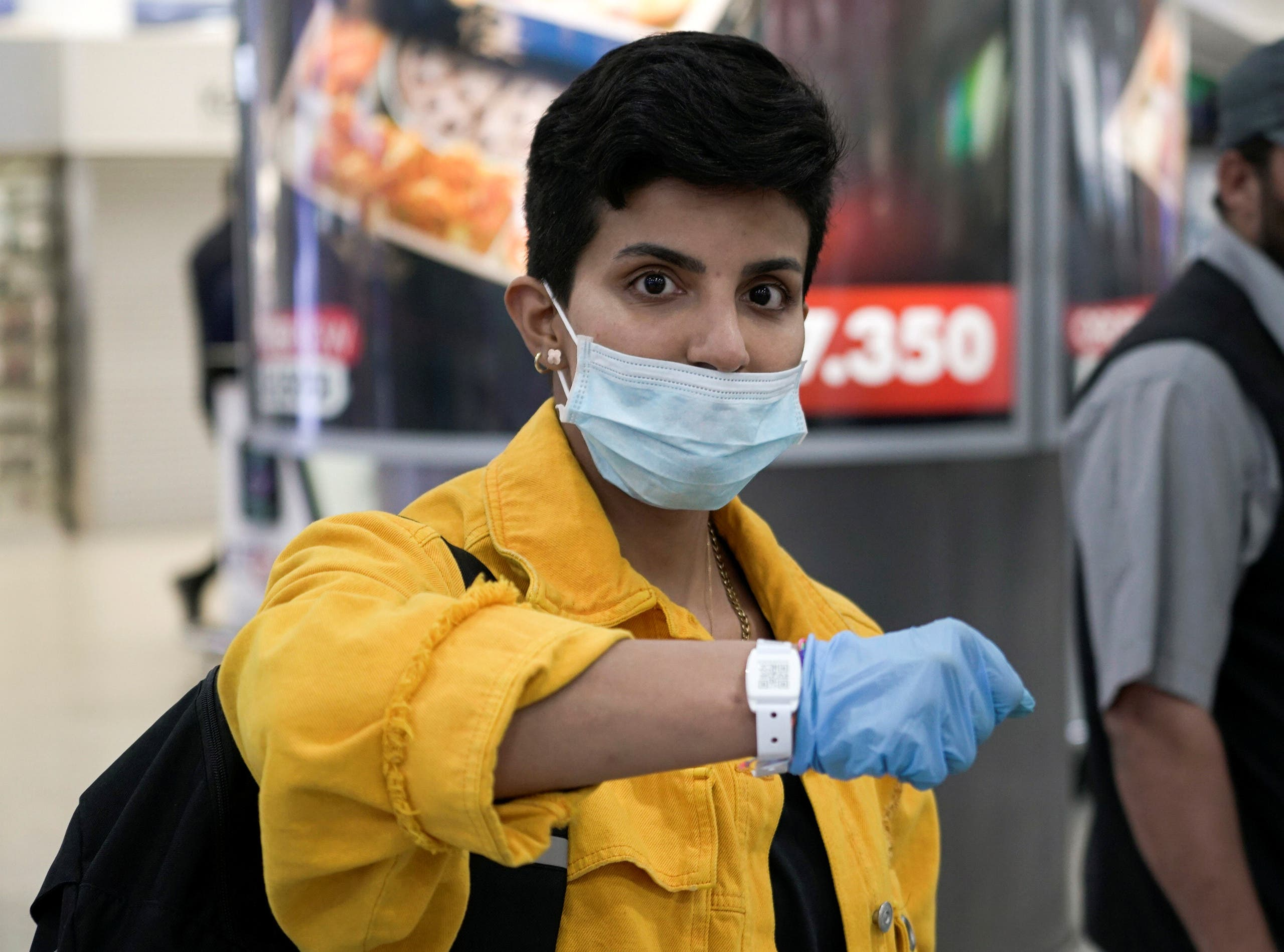 A Kuwaiti woman wearing a protective face mask poses as she shows her quarantine tracking bracelet upon her arrival from Amman to Kuwait Airport, following the outbreak of the coronavirus disease (COVID-19), in Kuwait City, Kuwait April 21, 2020. (Reuters)